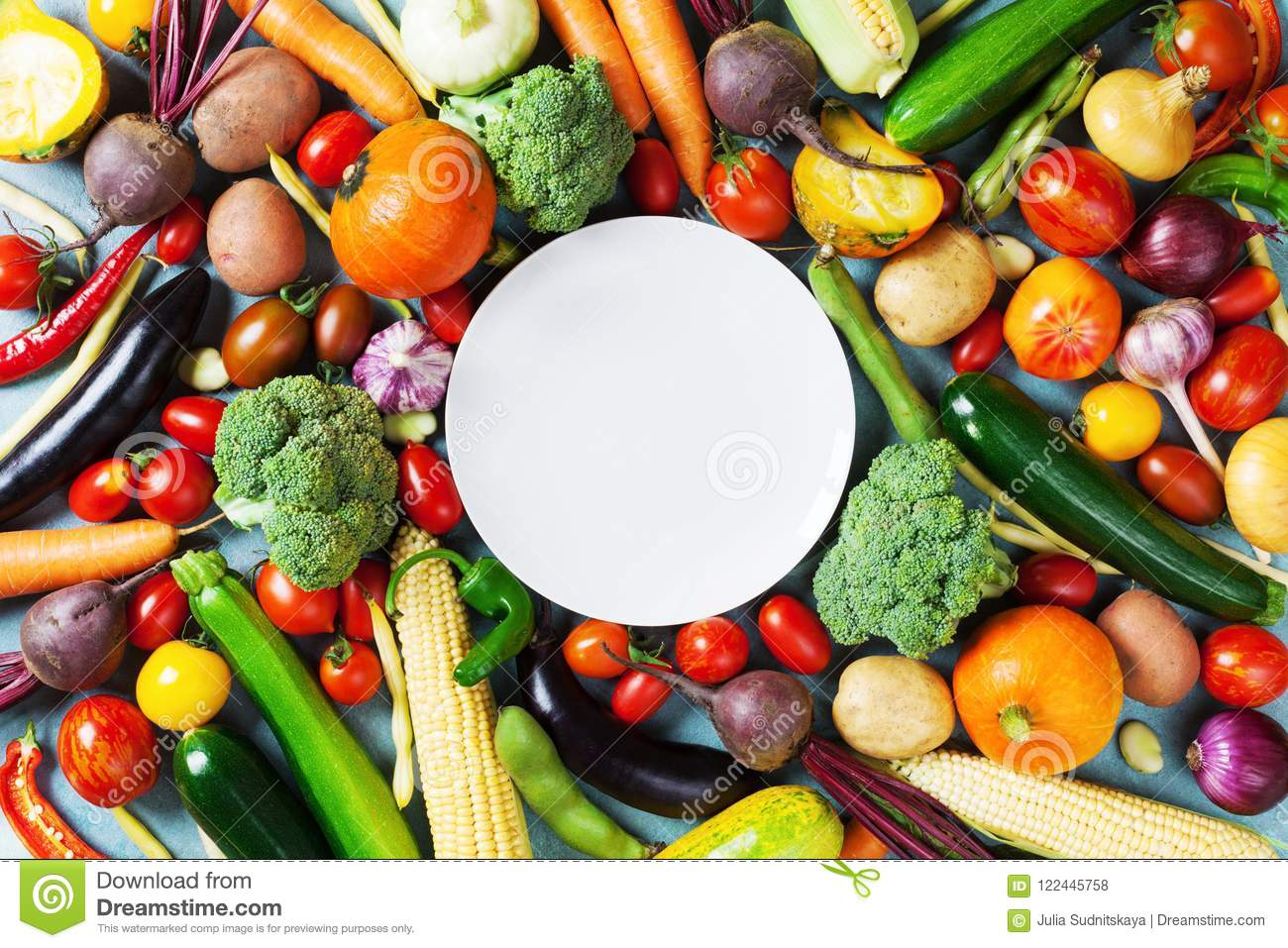 Autumn farm vegetables, root crops and white plate top view with copy space for menu or recipe. Healthy and organic food.