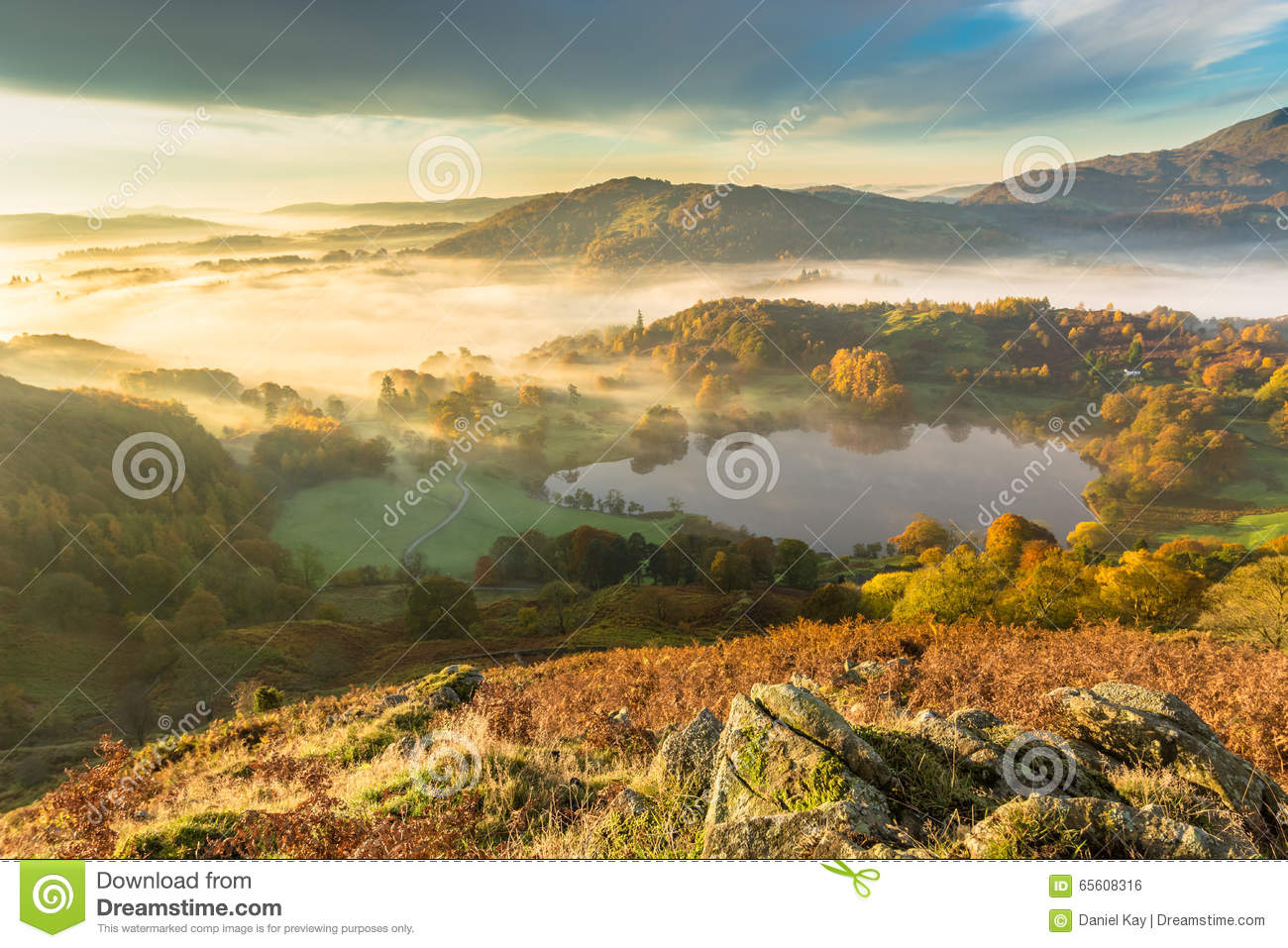 Autumn Fog Lingering Over Loughrigg Tarn In The English Lake District.