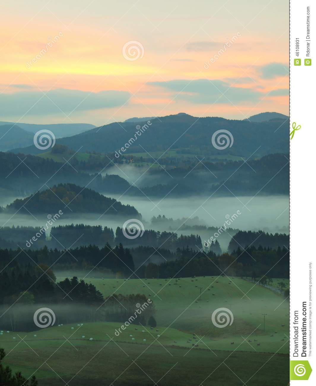 Autumn fogy countryside. View into long foggy valley full of colorful mist. Autumn melancholic landscape