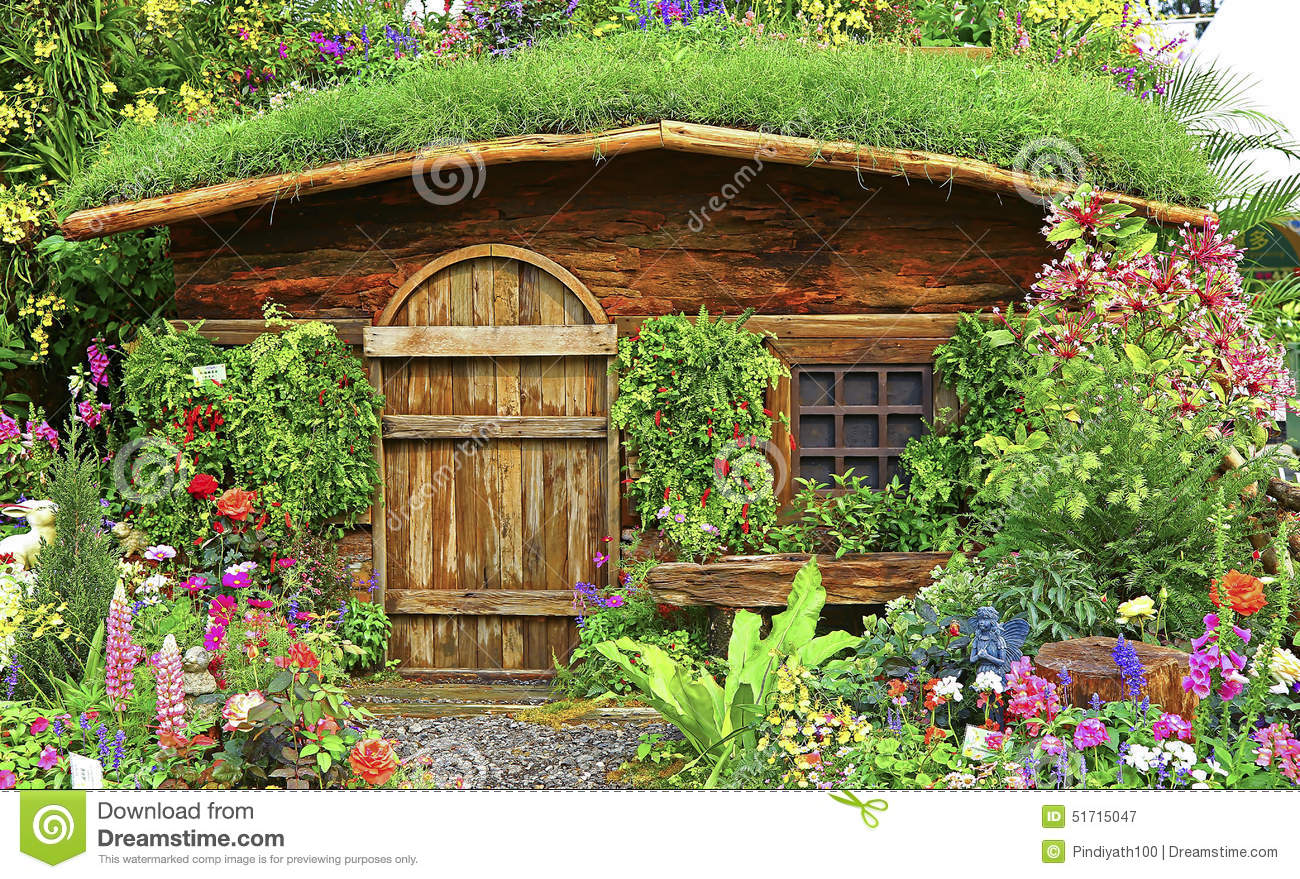 Autumn garden with wooden house or hut