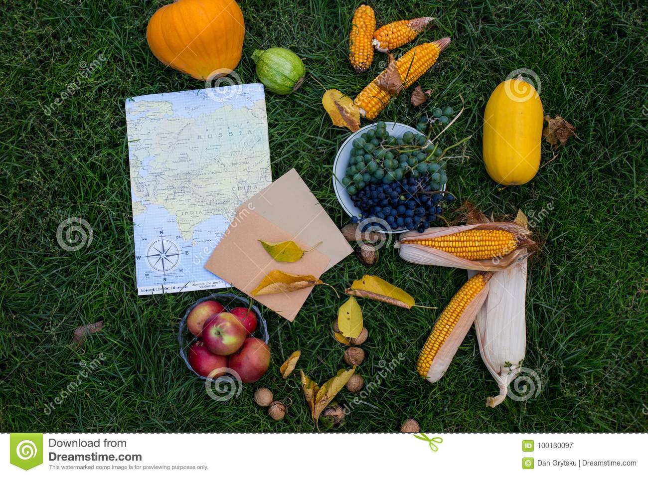 Autumn harvest on the green grass with map and latter. Autumn vegetable on the grass in composition. Map and vegetable. Hallo autu
