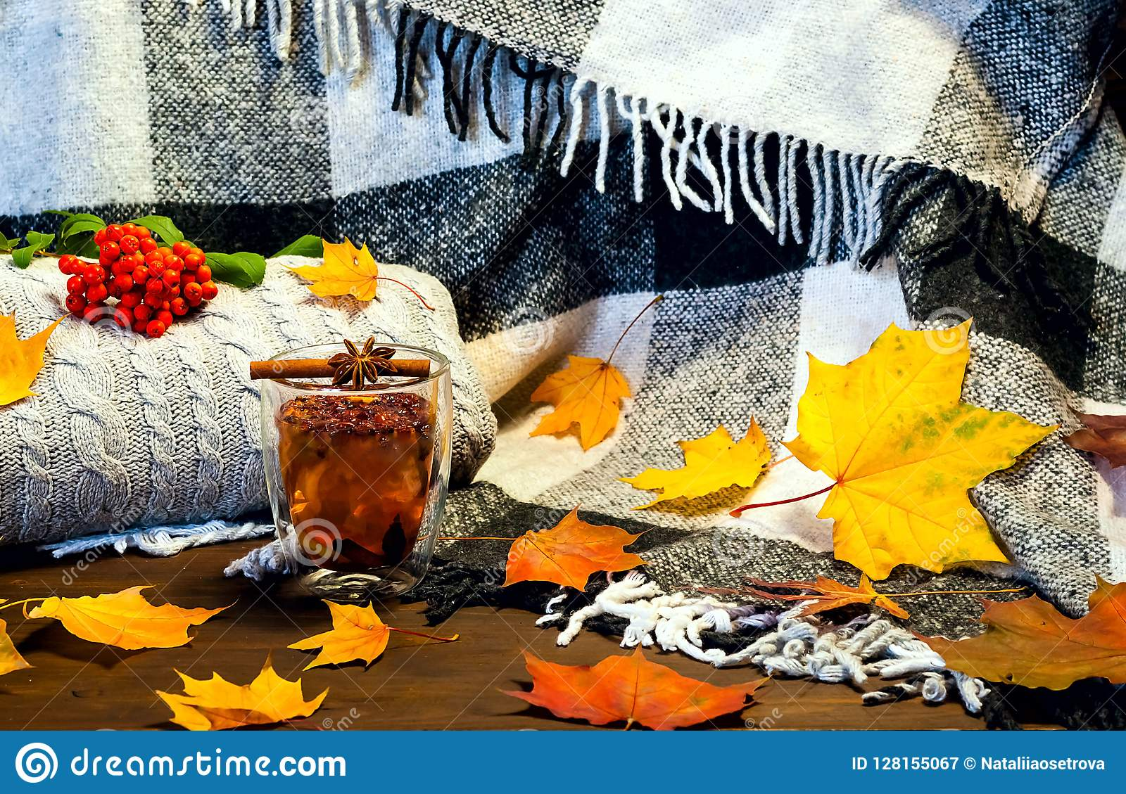 Autumn Home Decor.Glass Cup With Healing Tea And Cinnamon Sticks Amid  Bright Yellow Leaves
