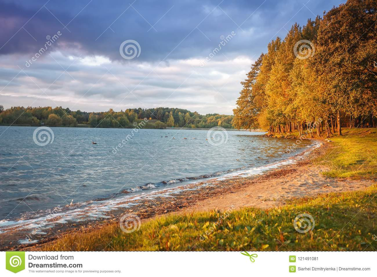 Autumn landscape of lake and colorful trees on shore in the evening. Yellow and red leaves on tree in october. Scenery of fall