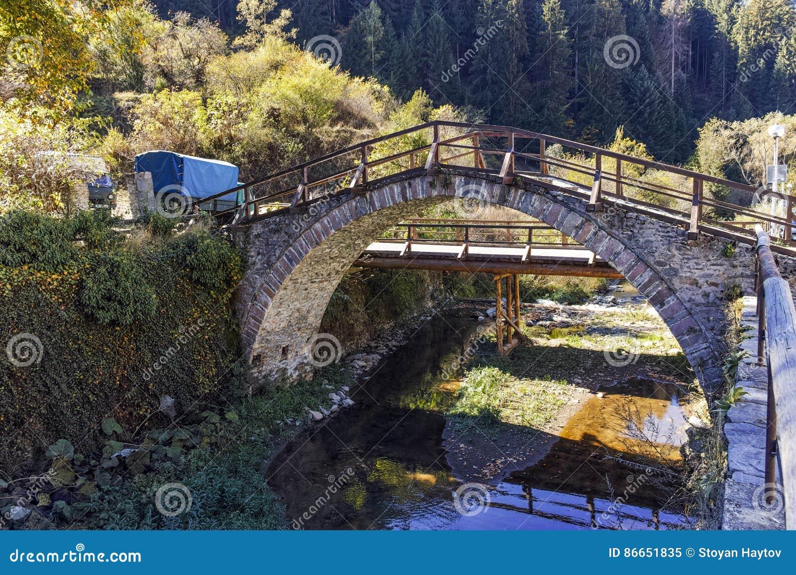 Autumn Landscape med Roman Bridge och gamla hus i stad av Shiroka Laka, Bulgarien