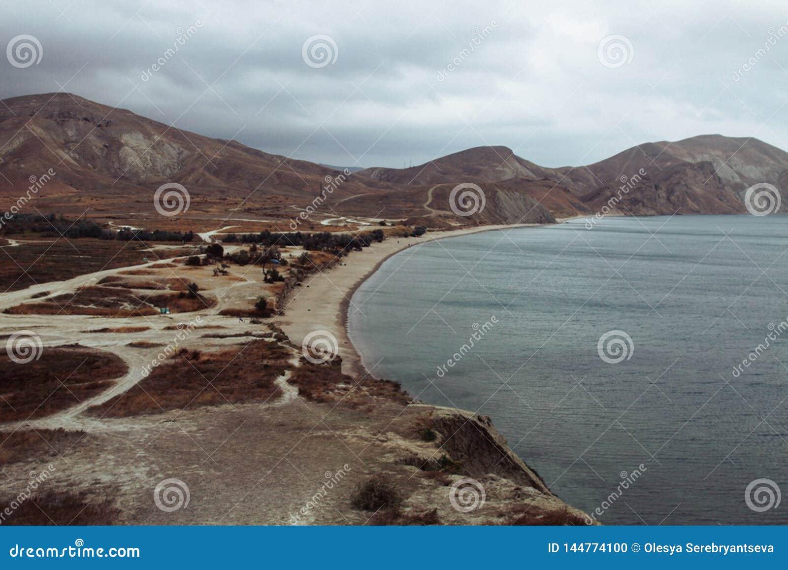 Landscape of seaside shore, Kara-Dag mountains in south winter day. Black Sea, Koktebel, Crimea