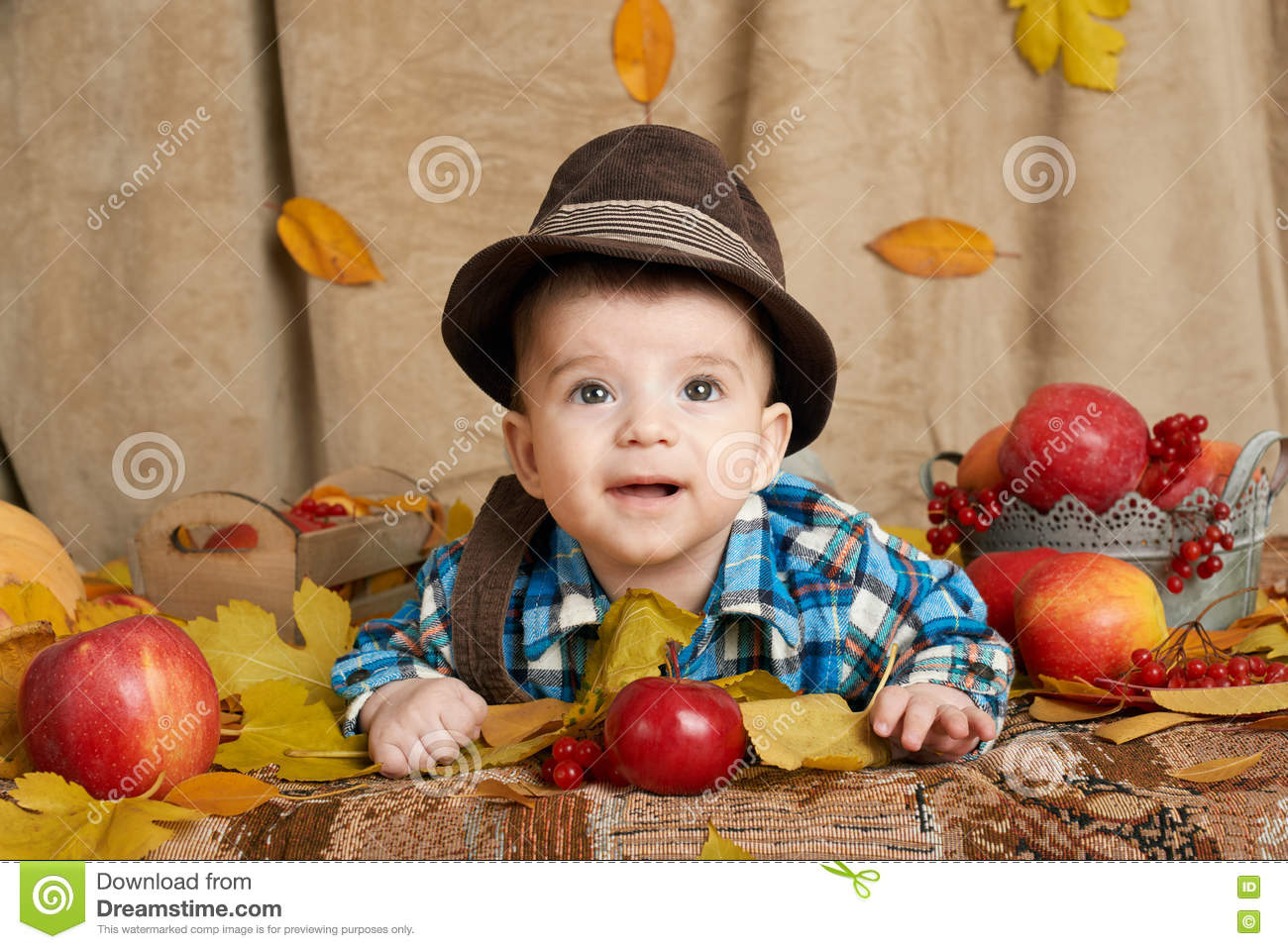 Autumn little child boy lie on yellow fall leaves, apples, pumpkin and decoration on textile