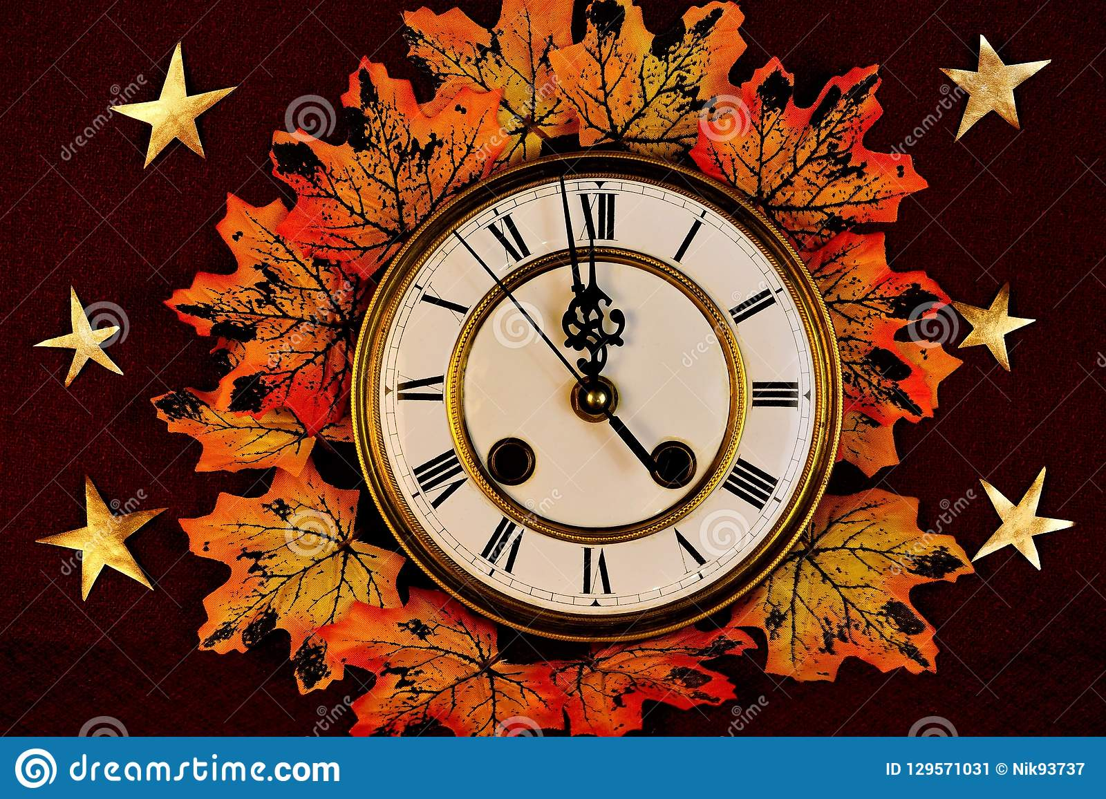 Autumn maple leaves, different colors of yellow, gold and red on the background of vintage watches,