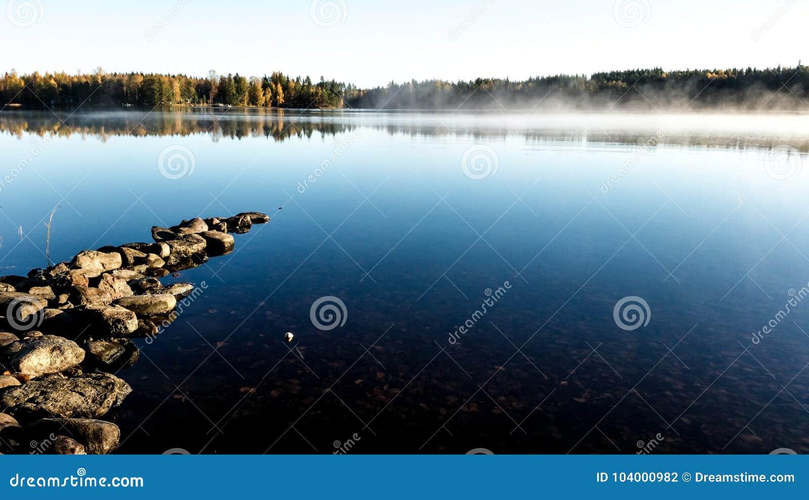 Autumn misty morning on the lake with golden lighten fog