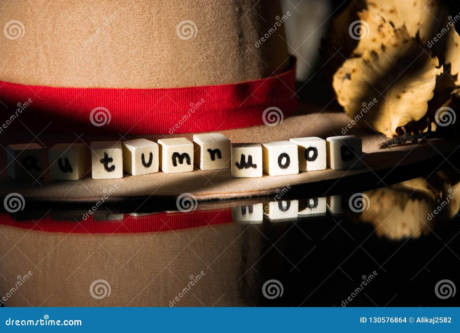 `Autumn mood` text phrase on female autumn hat on wooden background