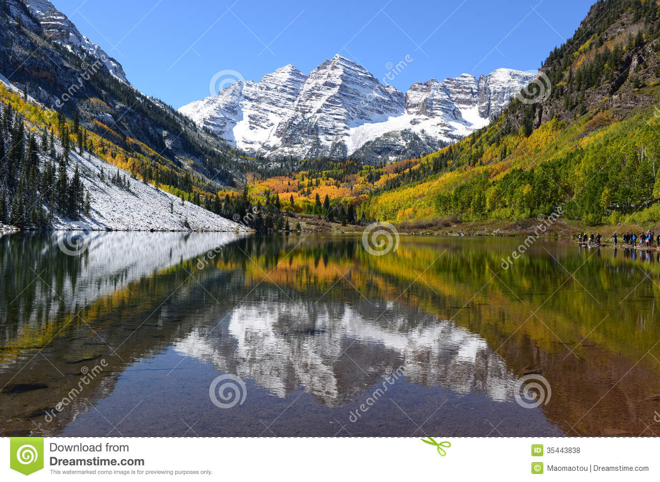 Autumn view of snow coated Maroon Bells and crystal clear Maroon Lake ...