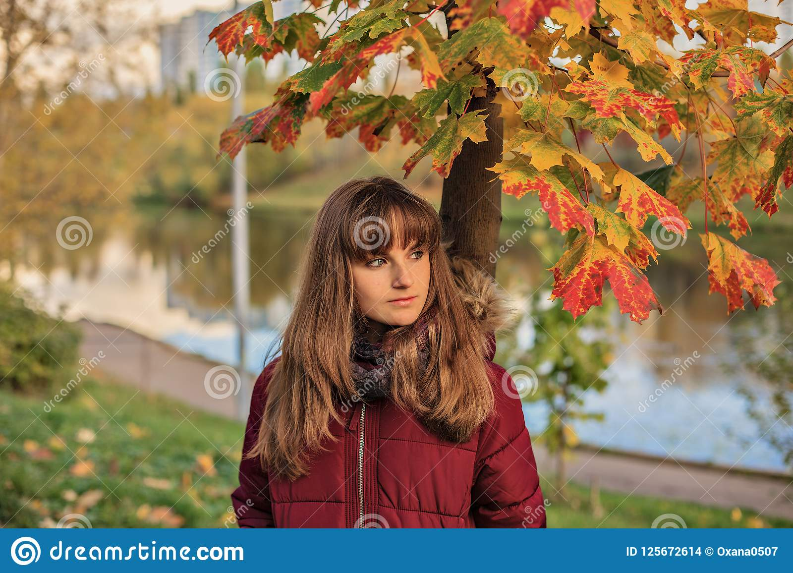 Teen girl standing near beautiful maple. close-up portrait of young redheaded girl in autumn forest.