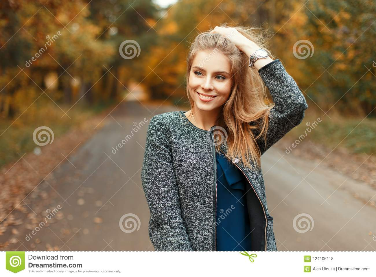 025c8ff90a Autumn portrait of a beautiful happy woman with a smile in fashionable  clothes in the park
