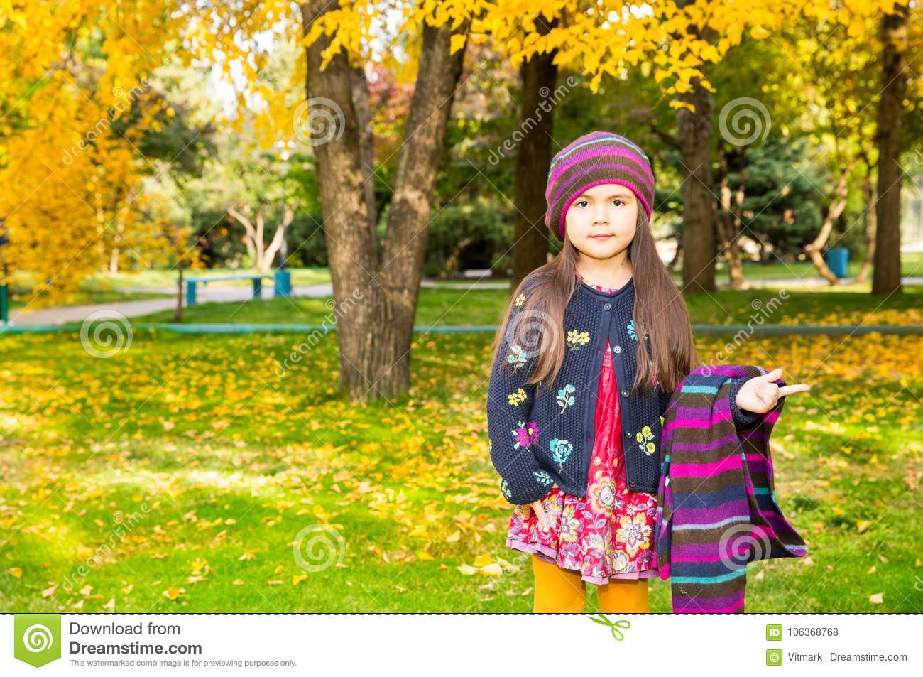 Autumn portrait of beautiful kazakh, asian child. Happy little girl with leaves in the park in fall.