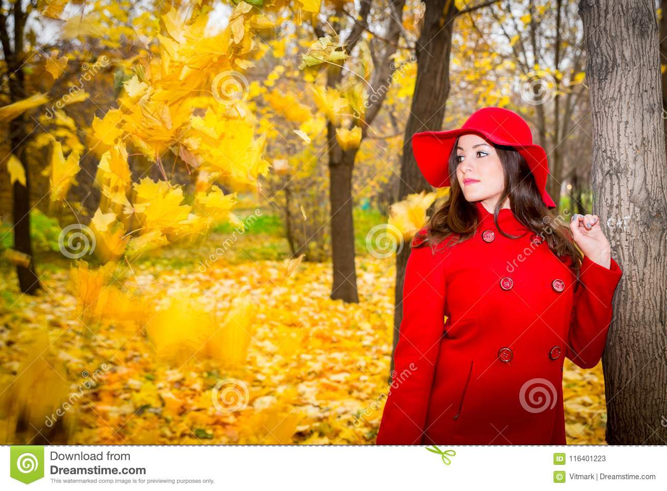 Autumn portrait of beautiful woman over yellow leaves while walking in the park at fall. Positive emotions and happiness concept.