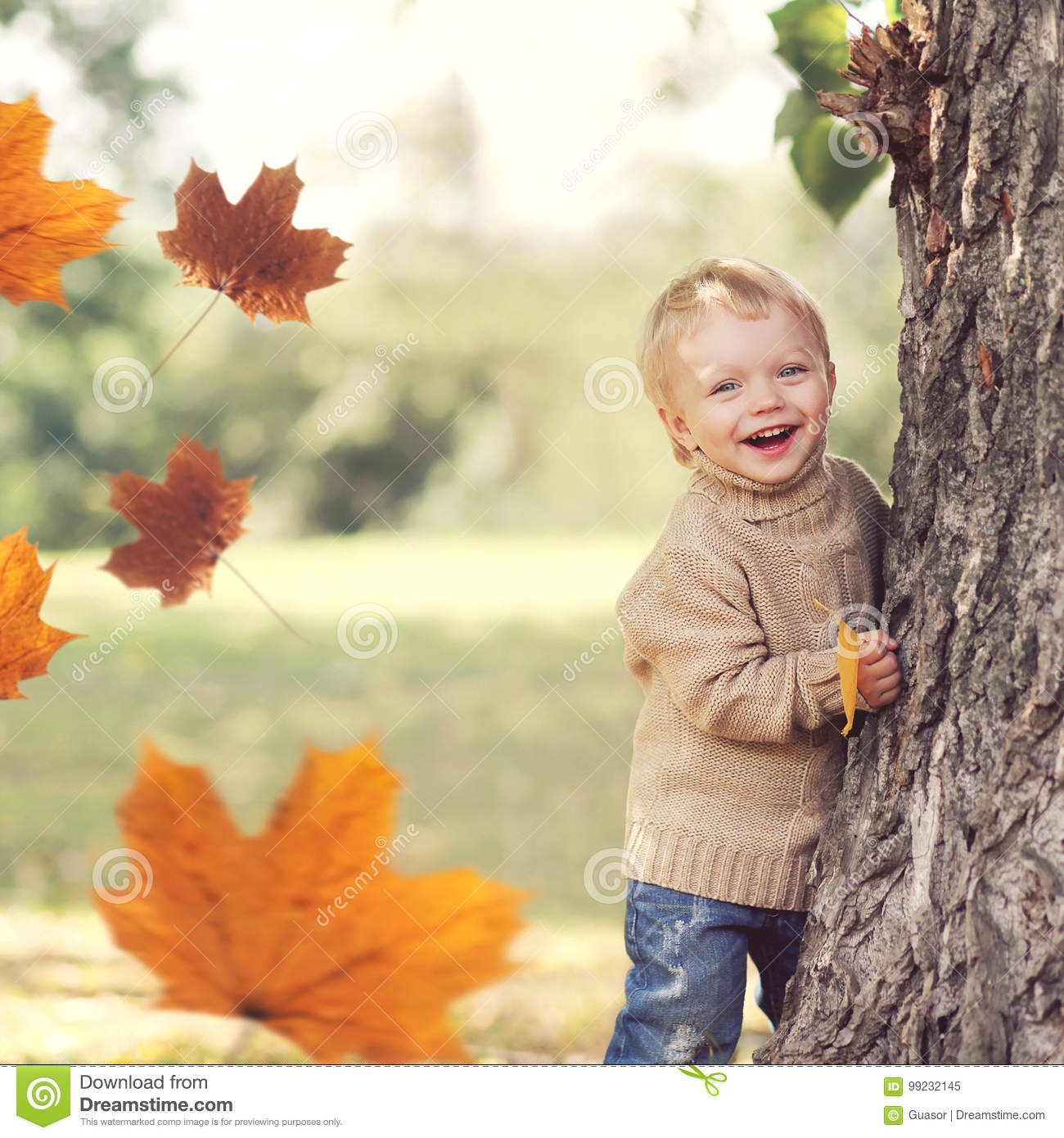 Autumn portrait of happy child playing having fun with flying yellow maple leaves