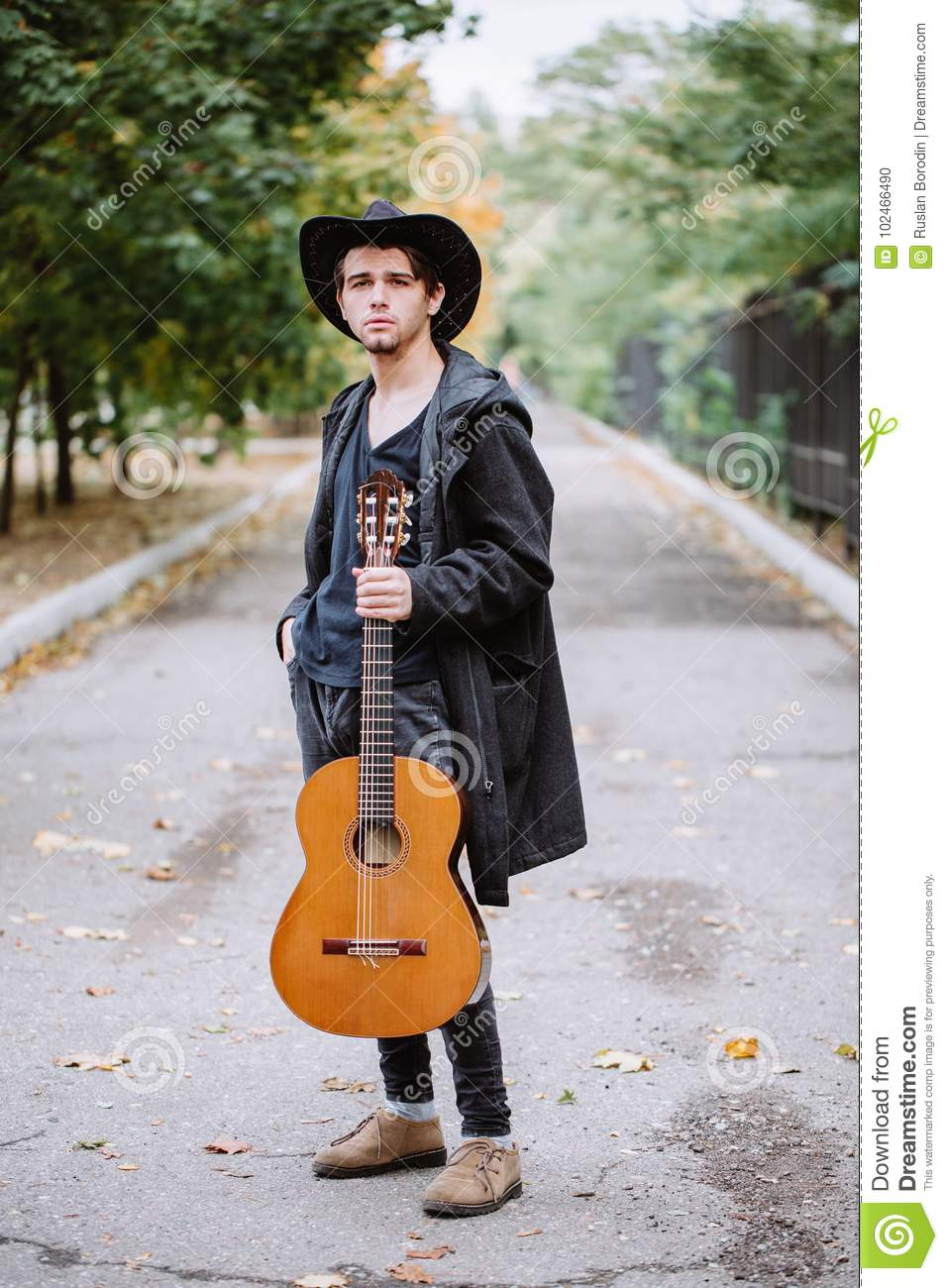 Autumn portrait of the young guy with guitar
