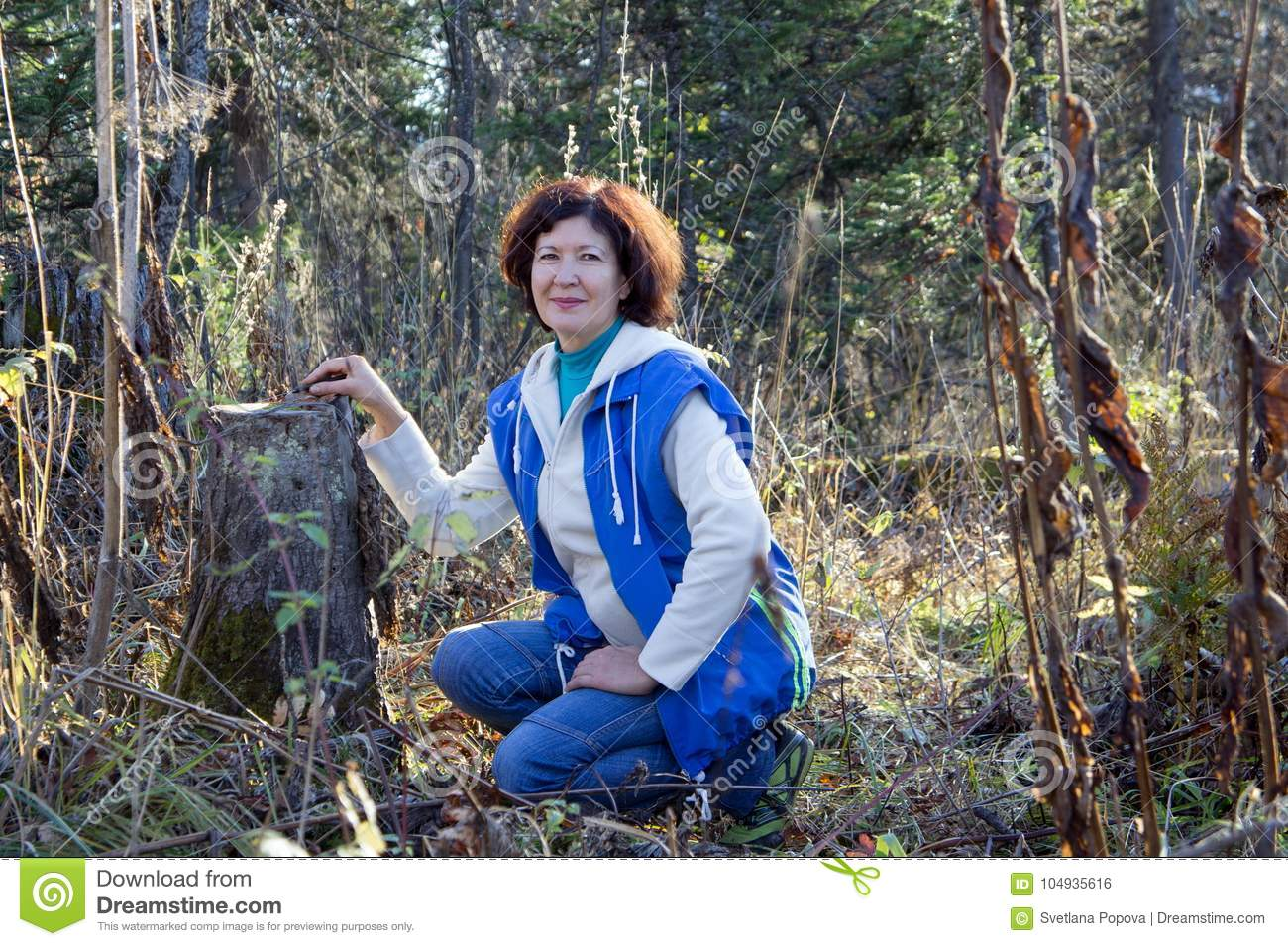 A happy woman sits beside the stump in the autumn forest.