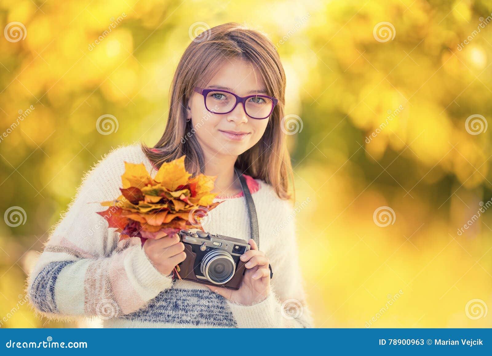 Autumn Time La ragazza sveglia attraente adolescente con il mazzo di autunno e la retro macchina fotografica Stagione di autunno