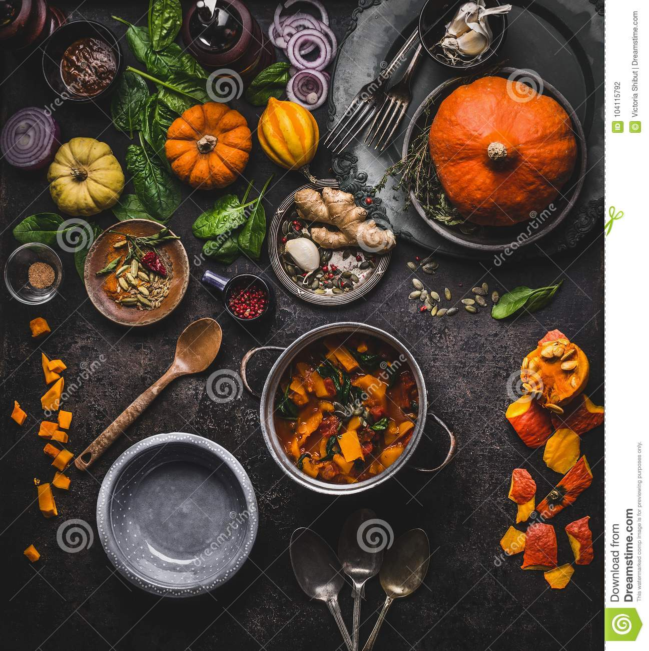 Autumn and winter cooking and eating with pumpkin dishes. Vegetarian stew in cooking pot with spoon and vegetables ingredients on