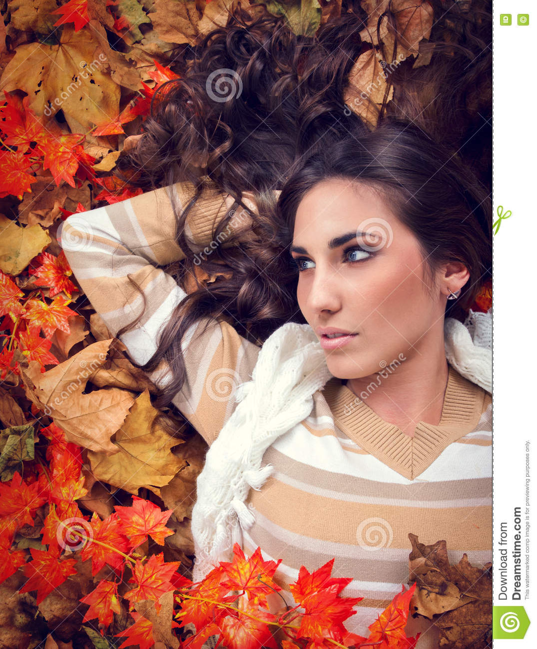 Autumn woman lying in orange leaves