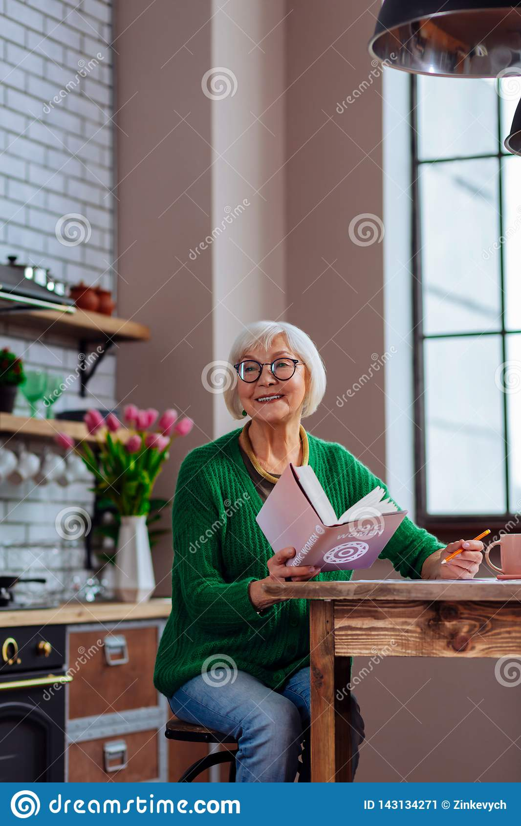 Avó bonita que sorri a alguém que chama ao manter um livro