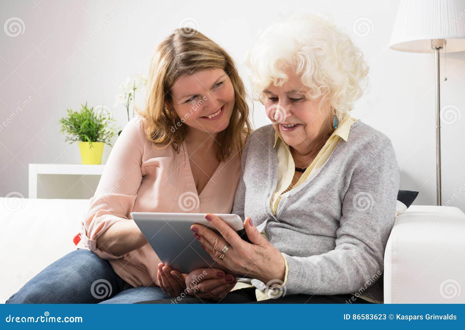 Avó de ensino da neta como usar a tabuleta