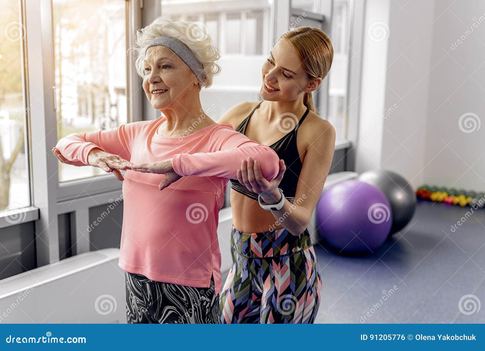 Avó de sorriso que faz exercícios com instrutor