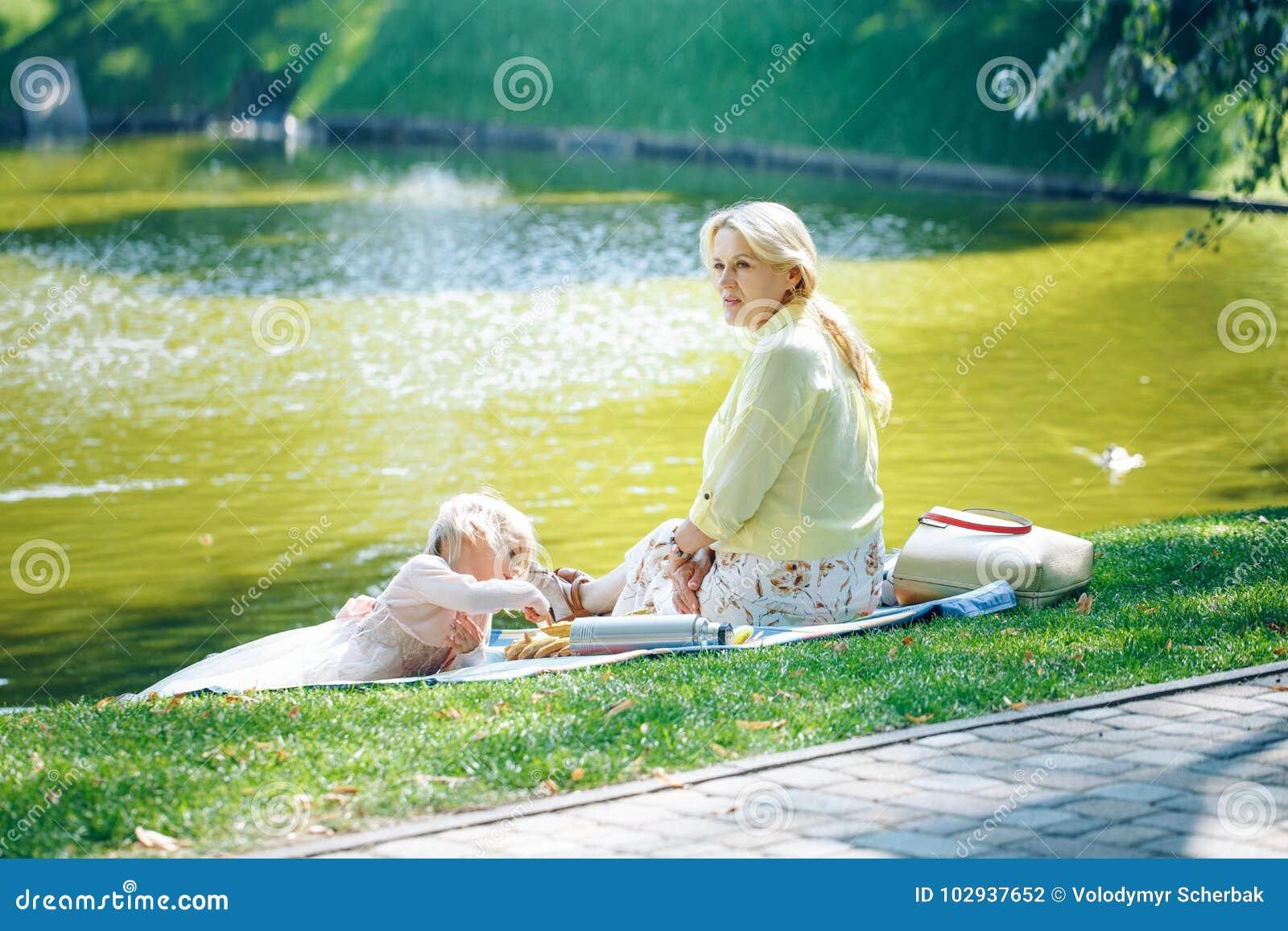 Avó e neta que apreciam o piquenique em um parque perto da água Avó que joga com a menina pequena da criança em um outono ensolar