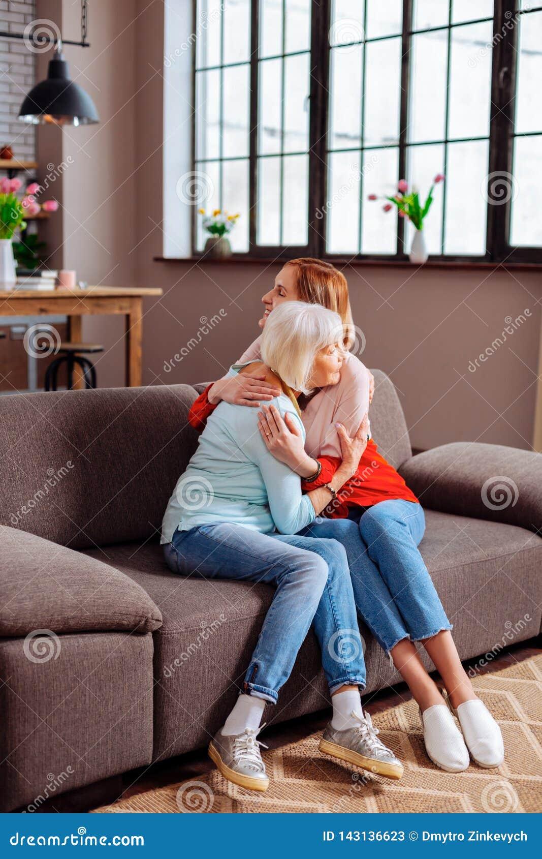 Avó idosa que tem um abraço com a neta atrativa no sofá