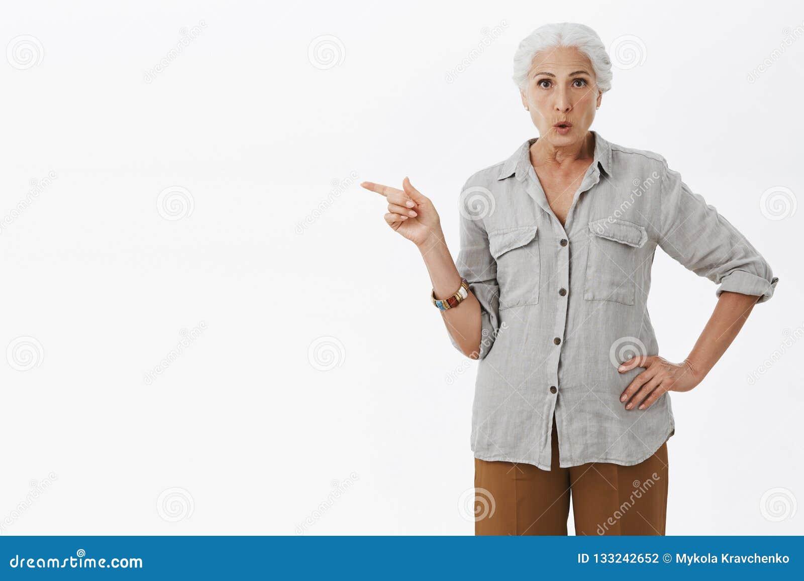 A avó intrigada com cabelo cinzento na mão fraca ocasional da terra arrendada da camisa em apontar da cintura deixou os bordos cu
