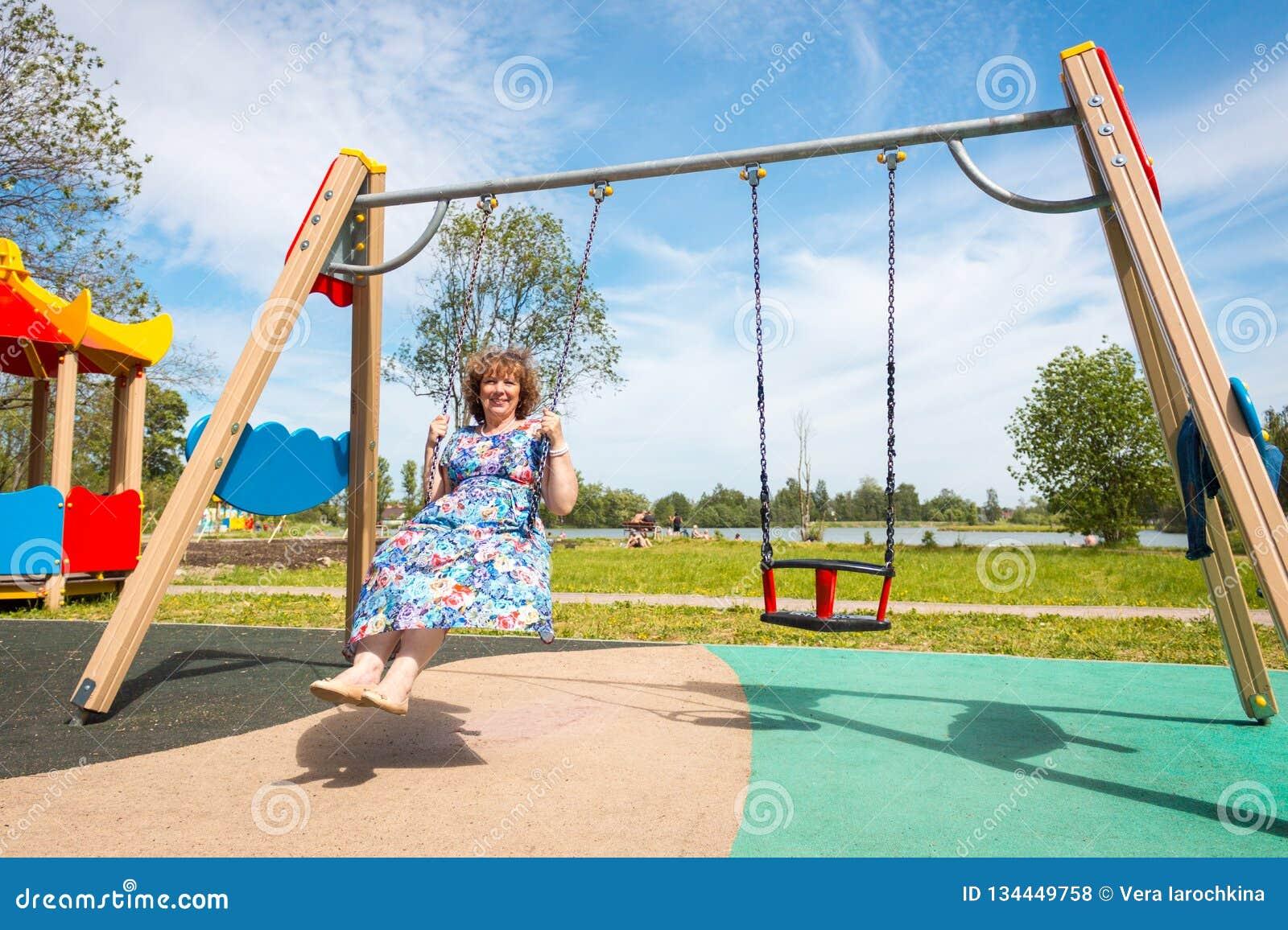 Avó mulher adulta que monta um balanço no campo de jogos