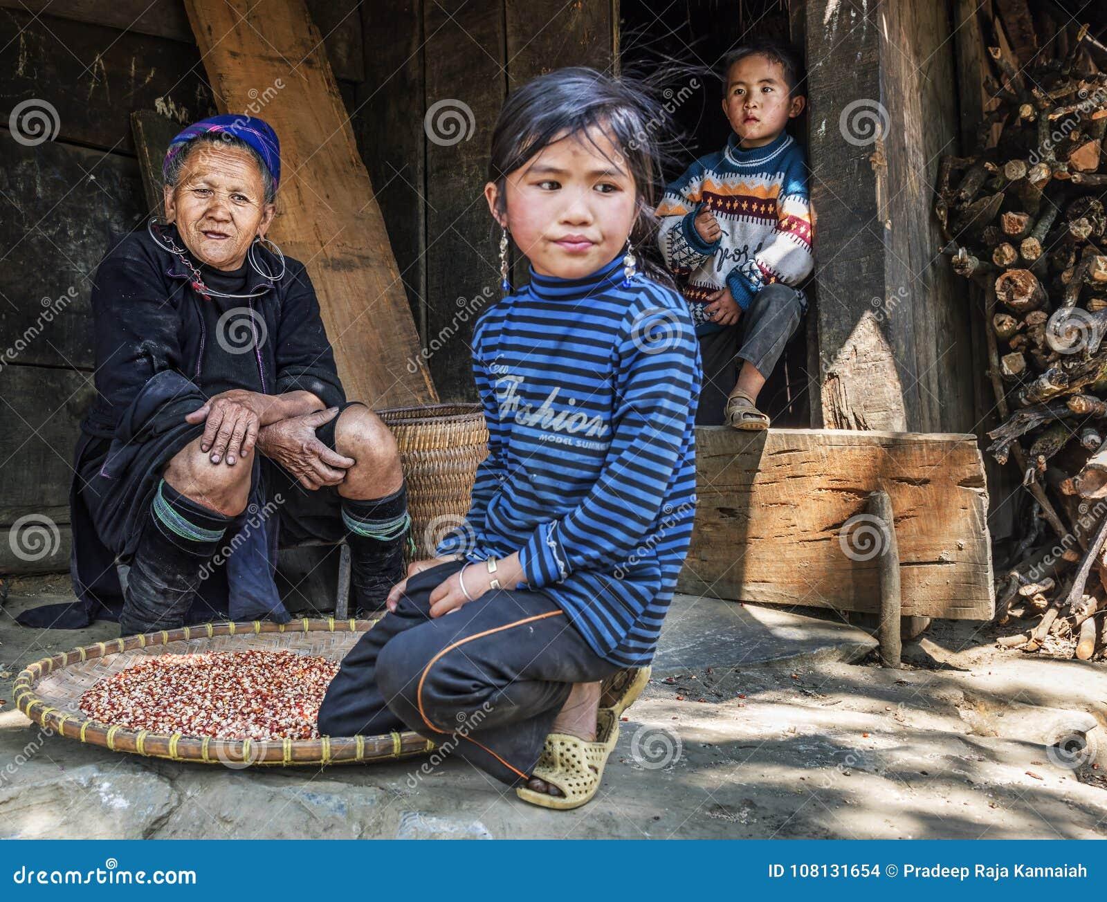 Avó que descansa fora de sua casa com seus dois netos em uma vila pequena, Sapa do tribo de Hmong, Vietname