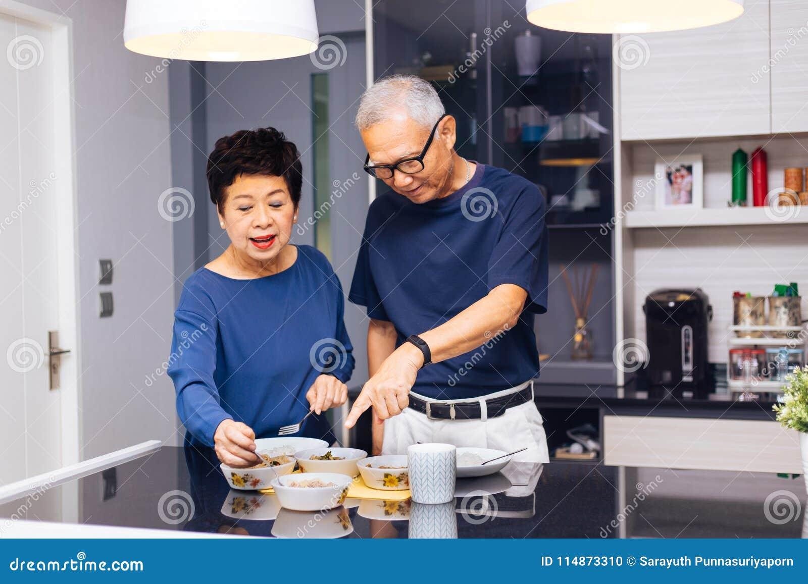 Avós asiáticas superiores dos pares que cozinham junto quando a mulher alimentar o alimento ao homem na cozinha Relacionamento du