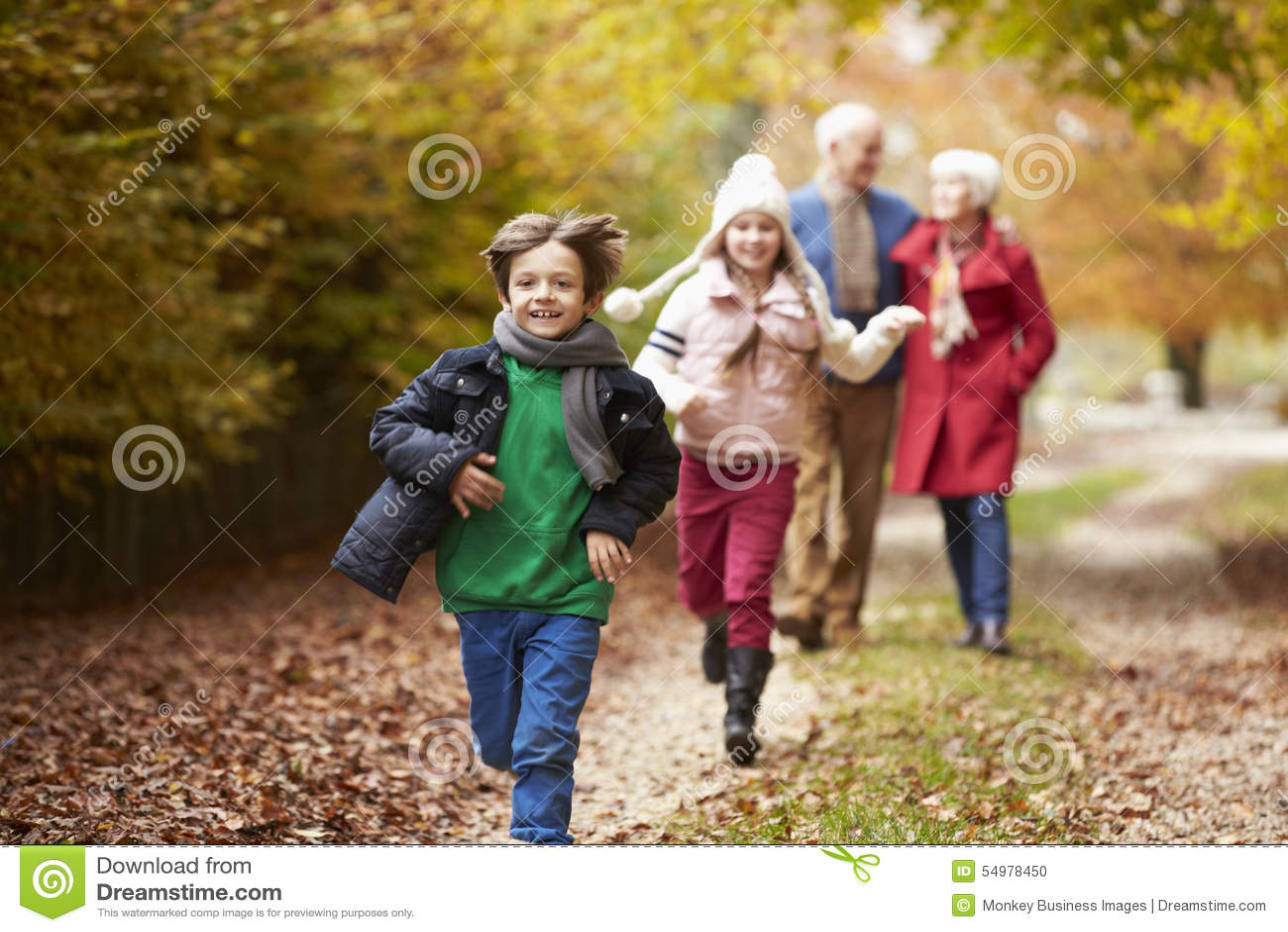 Avós com os netos que correm ao longo de Autumn Path