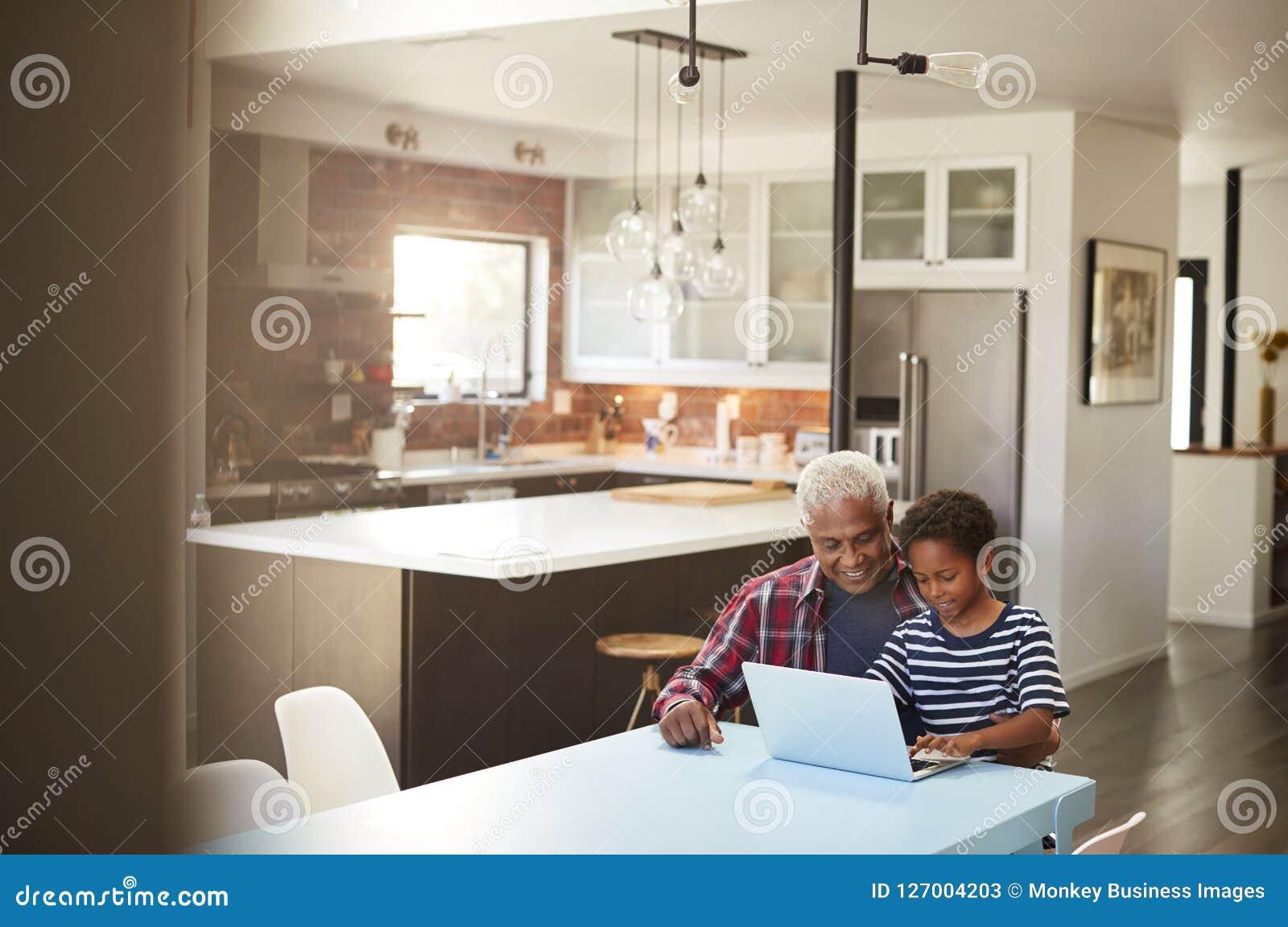 Avô e neto que sentam-se em torno da tabela em casa que usa o portátil junto