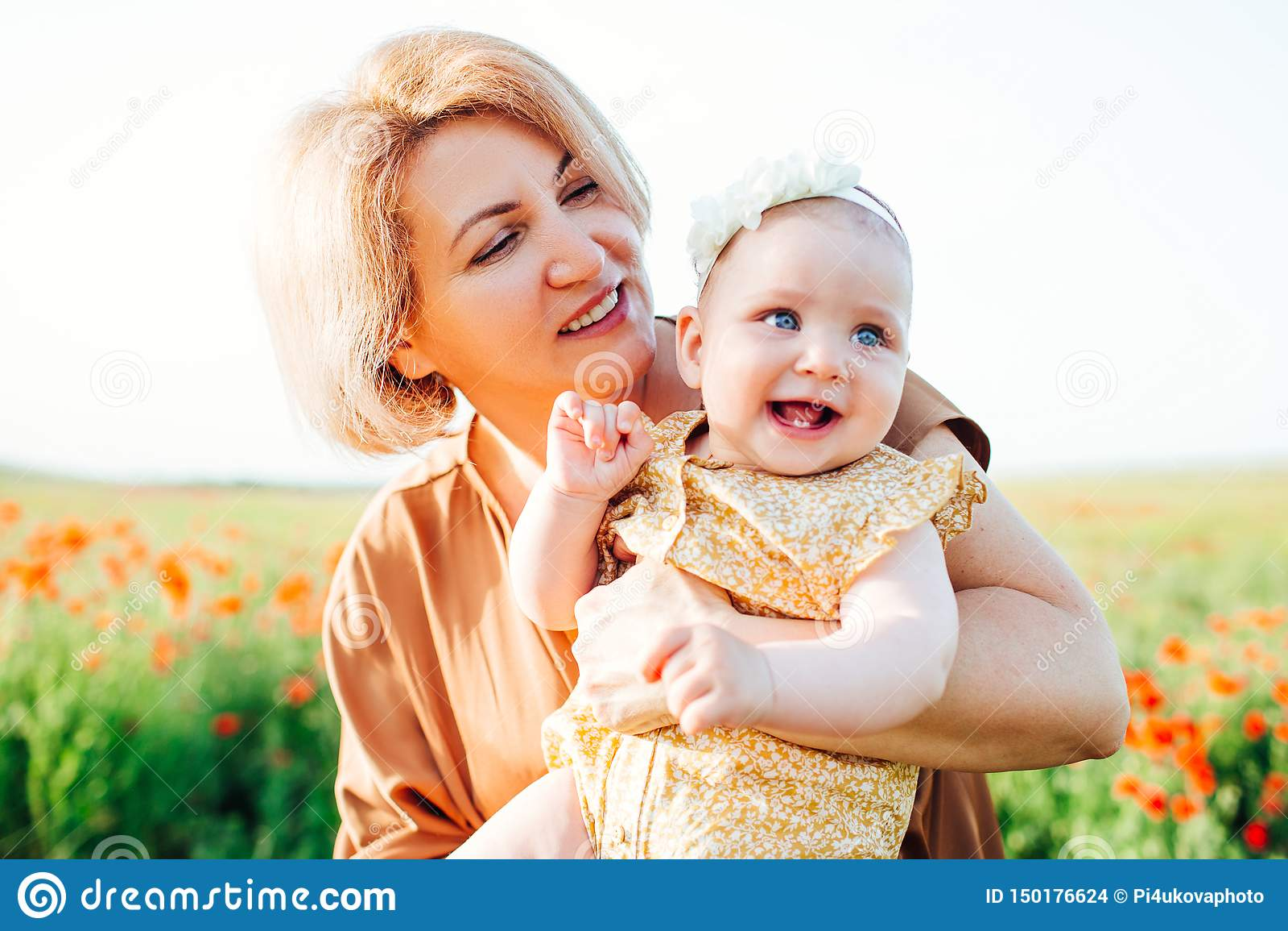 Av? com uma neta pequena que joga em um campo da papoila