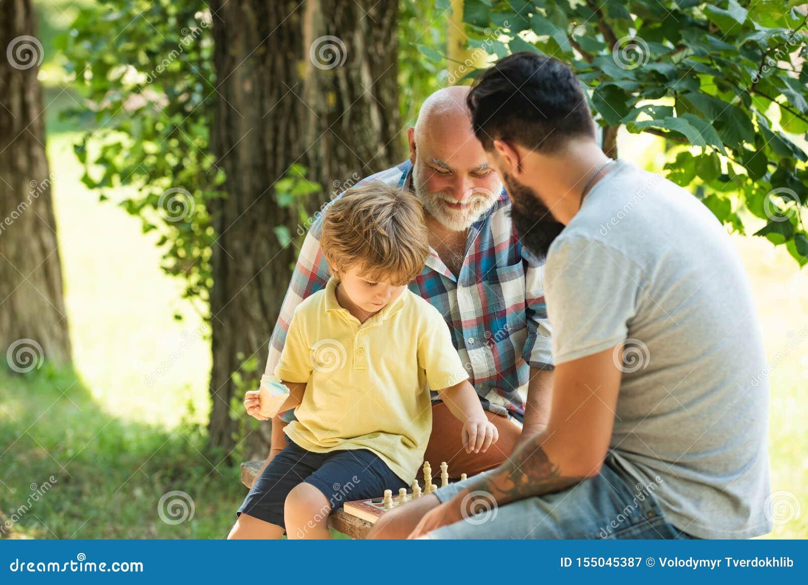 Av? e neto que jogam a xadrez O paizinho e o vovô com seu filho da criança estão jogando a xadrez Exercício do homem superior den