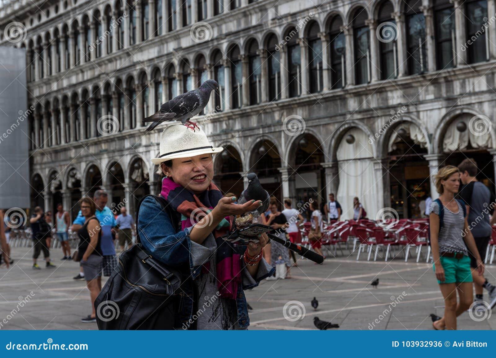 27 av Juni, St-fläckfyrkant, Venedig, Italien: Några duvor sitter på en japansk hatt för kvinna` s, det som försöks för att mata