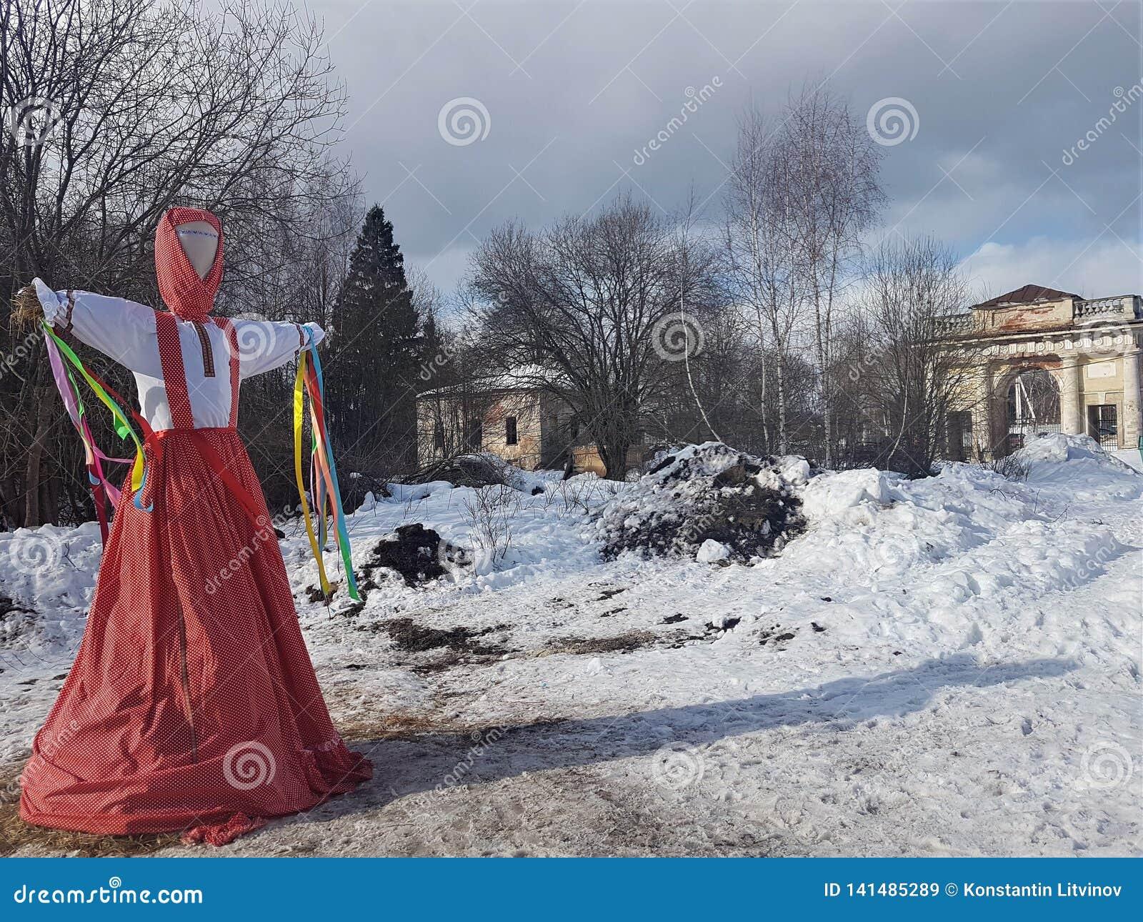 Avbildningen av Maslenitsa i rysk folk dräkt bränns i snön under den traditionella nationella ferien av moderavskedet