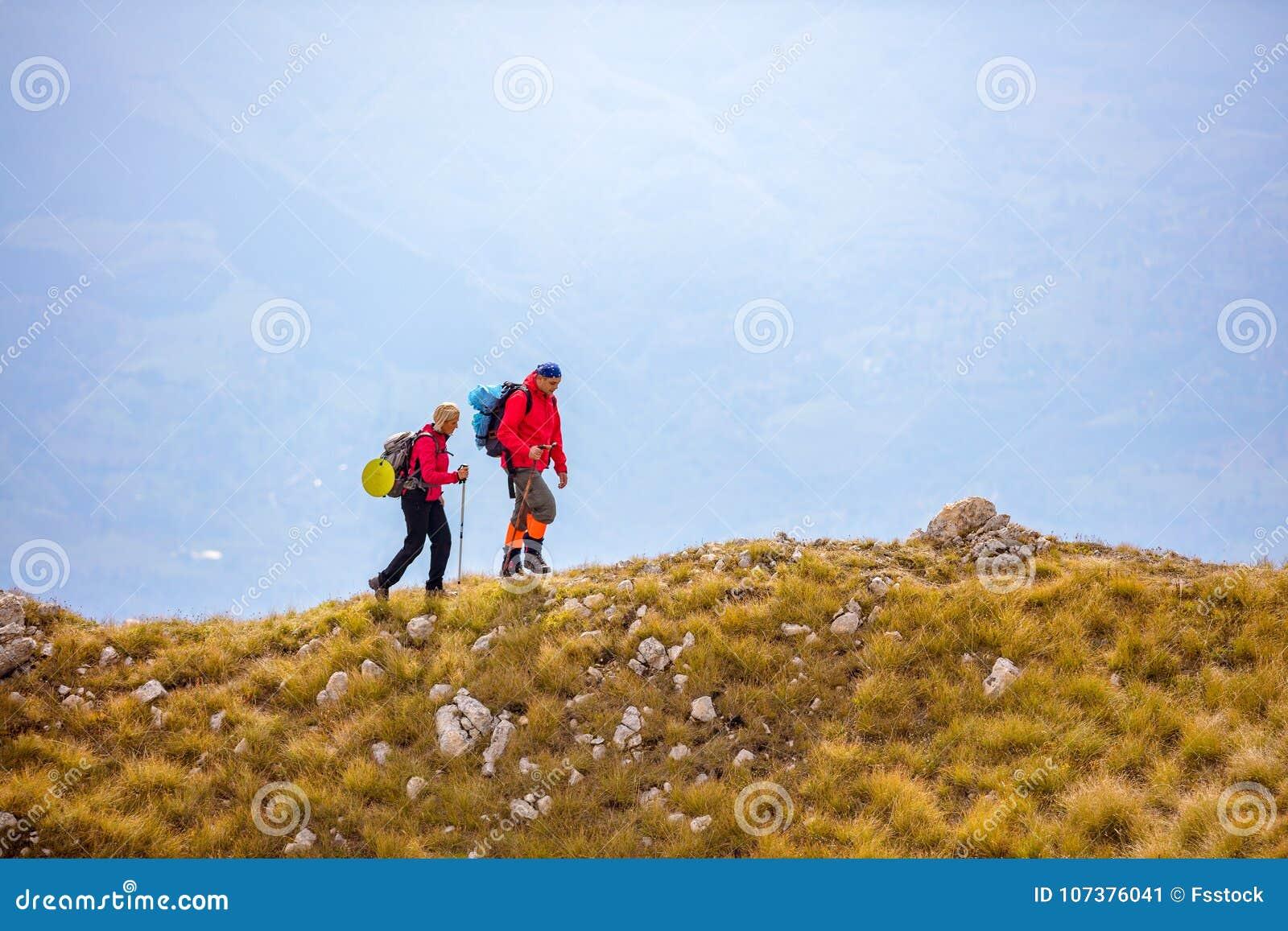 Aventúrese, viaje, turismo, alza y concepto de la gente - par sonriente que camina con las mochilas al aire libre