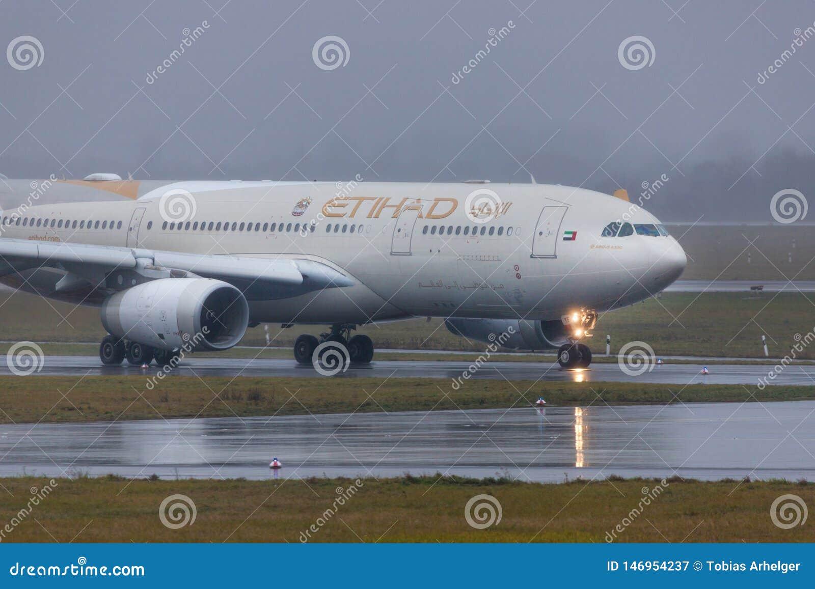 Avi?o das linhas a?reas de Etihad na terra no aeroporto Alemanha de dusseldorf na chuva