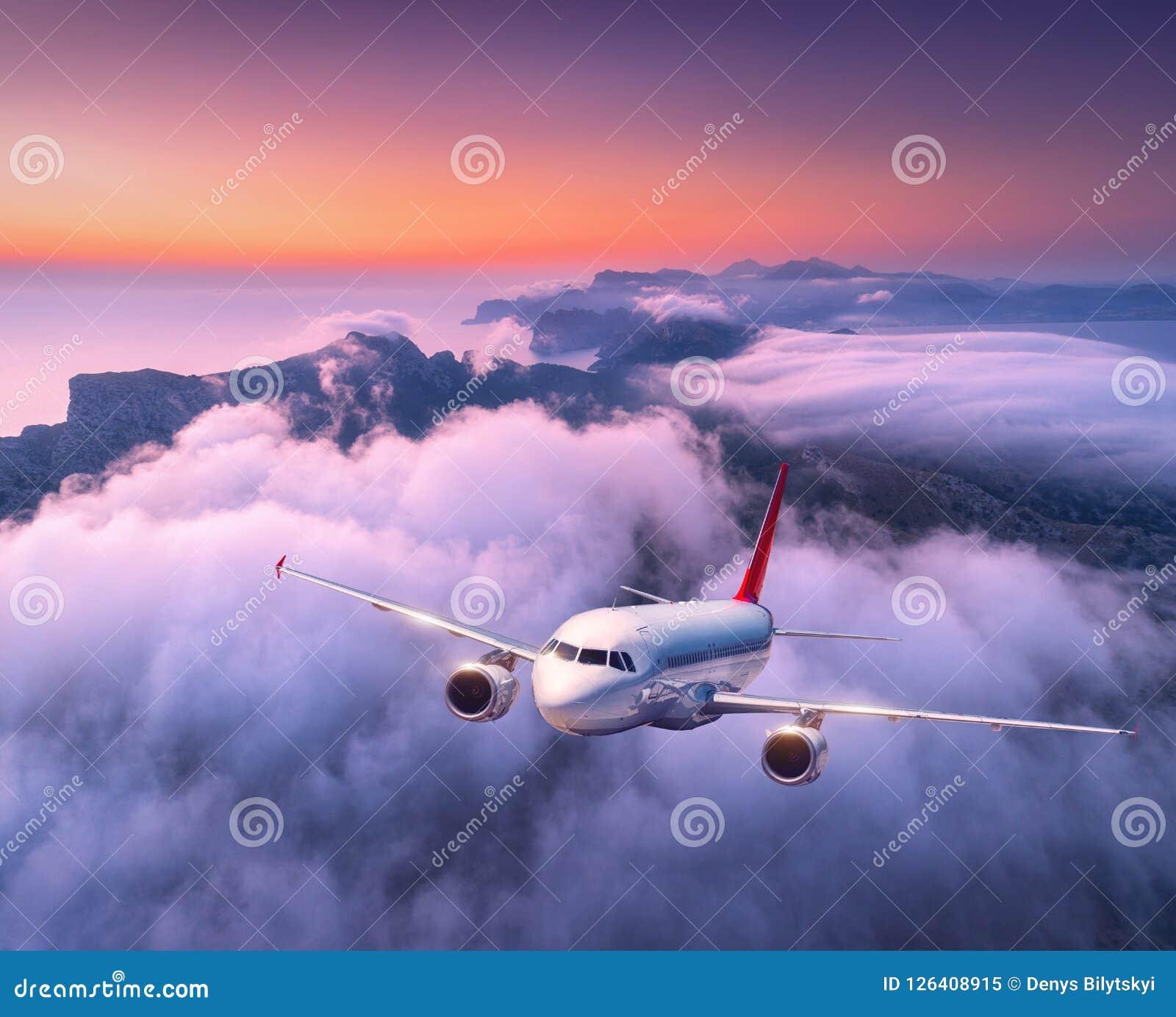 Avião do passageiro que voa sobre nuvens no por do sol Aviões