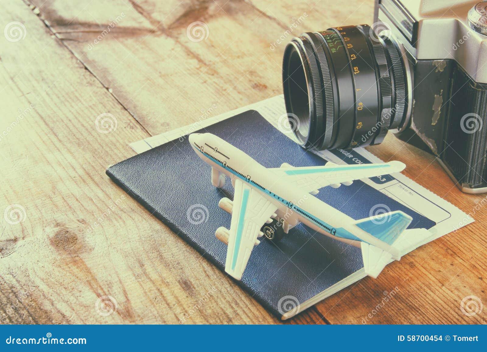 Avião e passaporte do brinquedo sobre a tabela de madeira Imagem retro do estilo