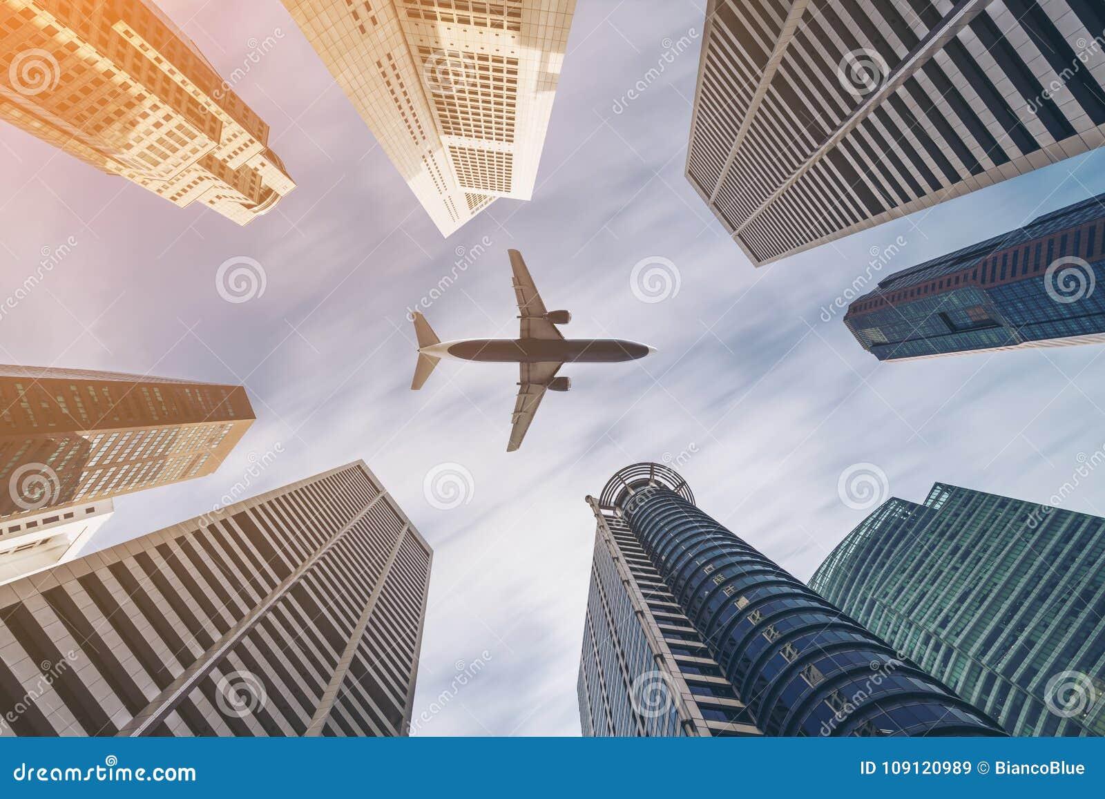 Avião que voa sobre construções do negócio da cidade, skyscrap do arranha-céus