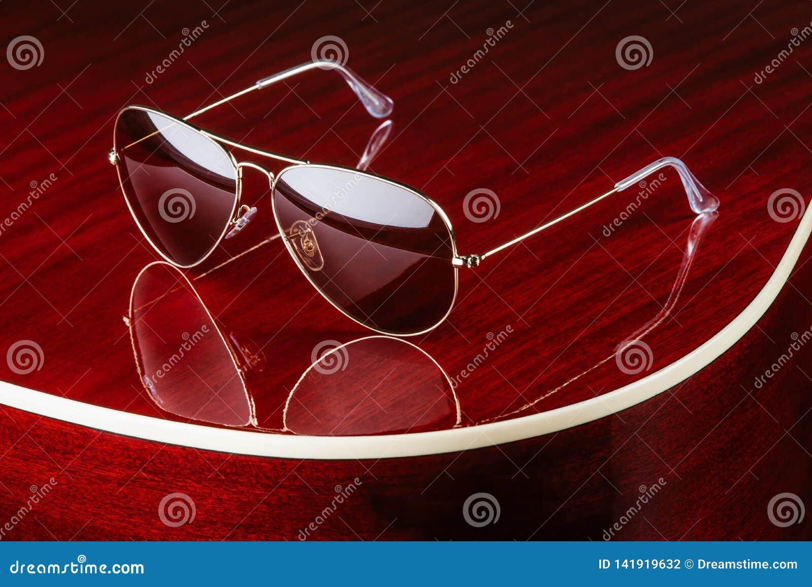 Aviator style sunglasses on glossy guitar