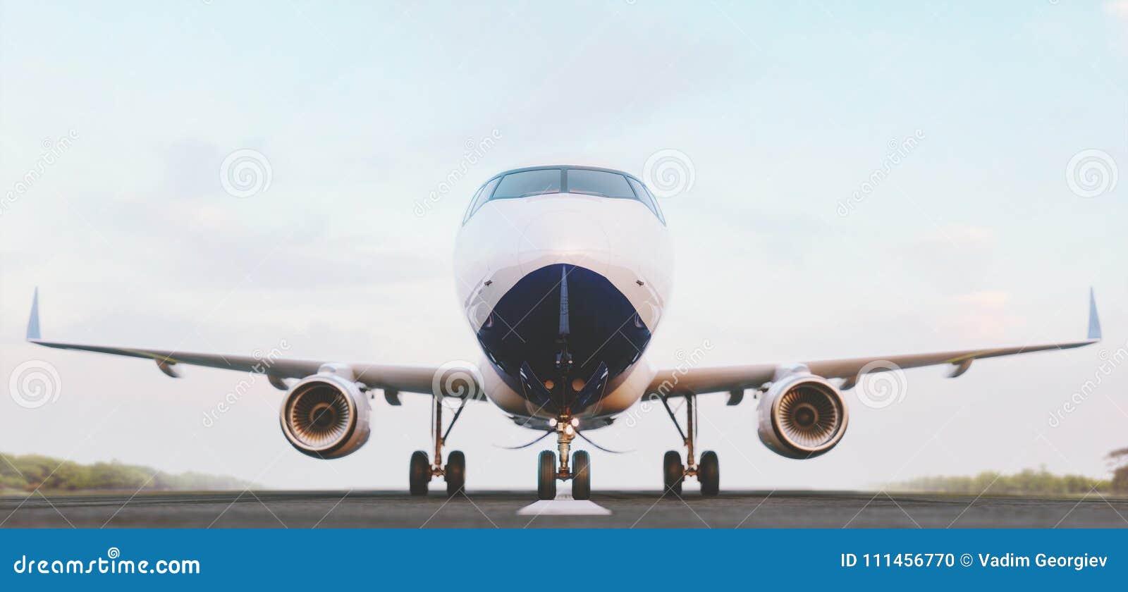 Avion commercial blanc se tenant sur la piste d aéroport au coucher du soleil La vue de face de l avion de passager décolle