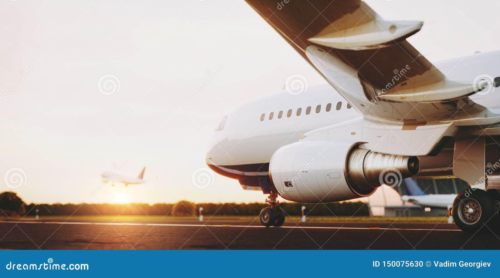 Avion commercial blanc se tenant sur la piste d a?roport au coucher du soleil L avion de passager d?colle