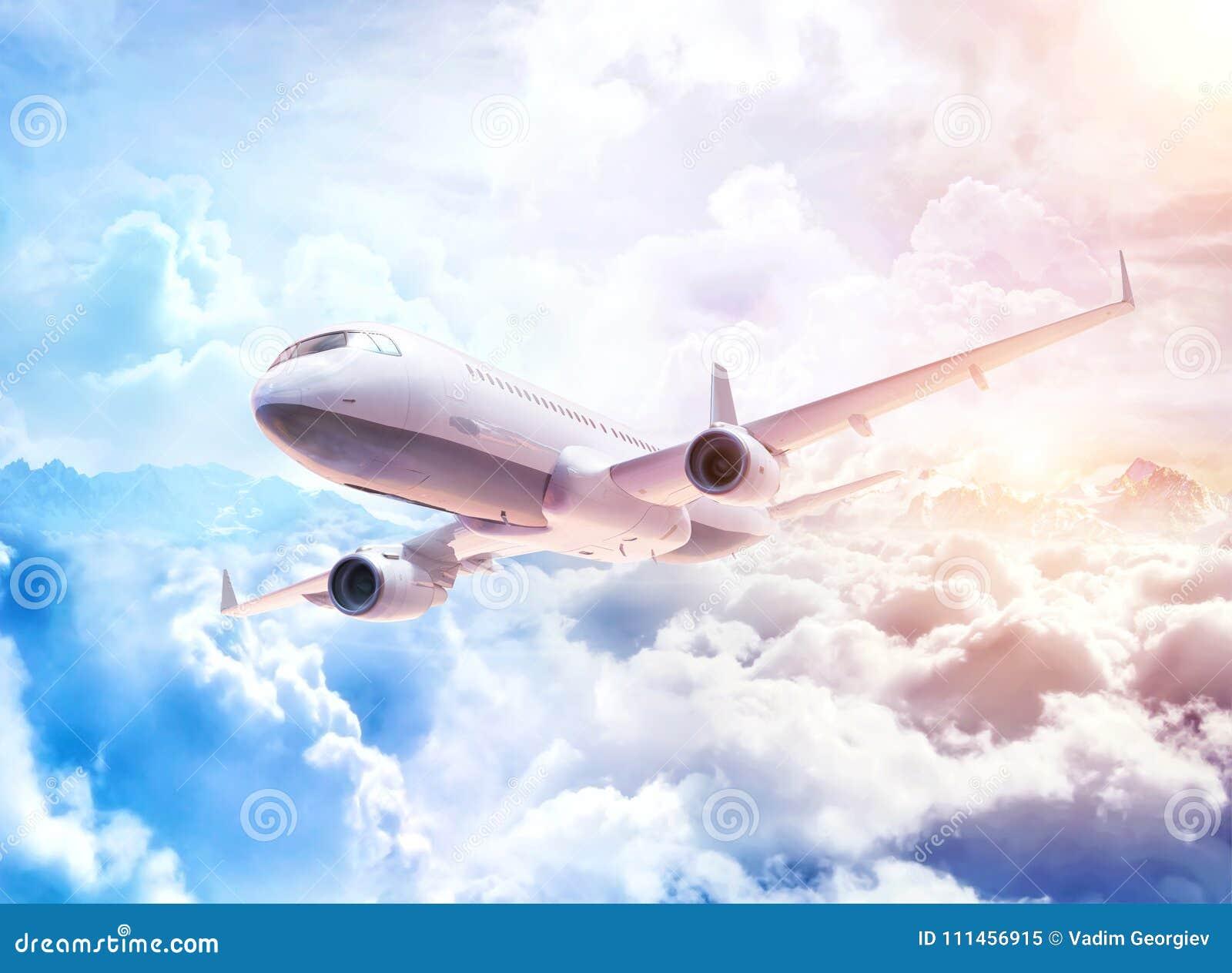 Avion commercial blanc volant au-dessus des nuages au fond fantastique avec des nuages et des crêtes de montagne