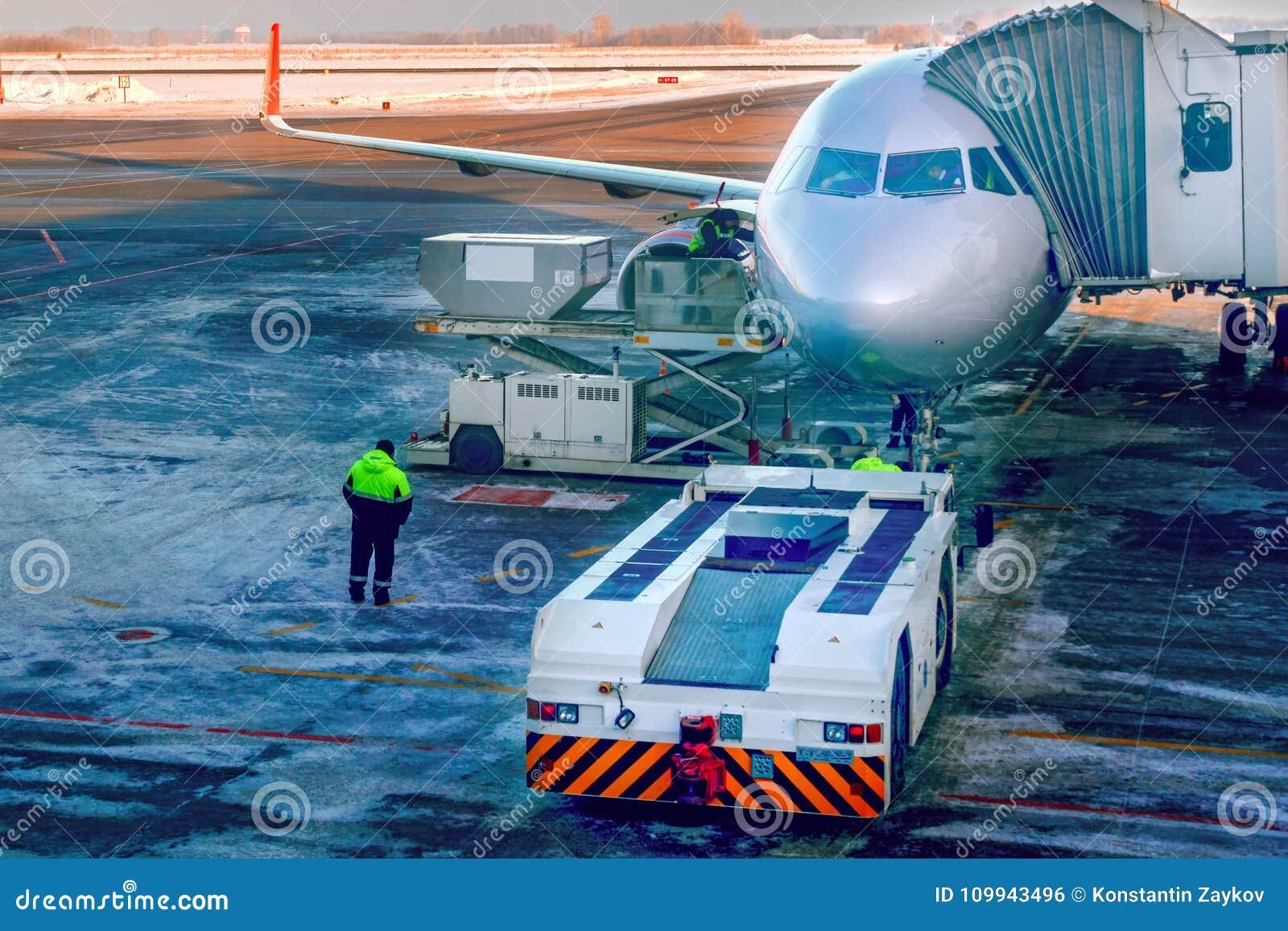 Aviones que son atados a la pasarela telescópica jetway o del pasajero en el delantal del aeropuerto Se prepara para los pasajero