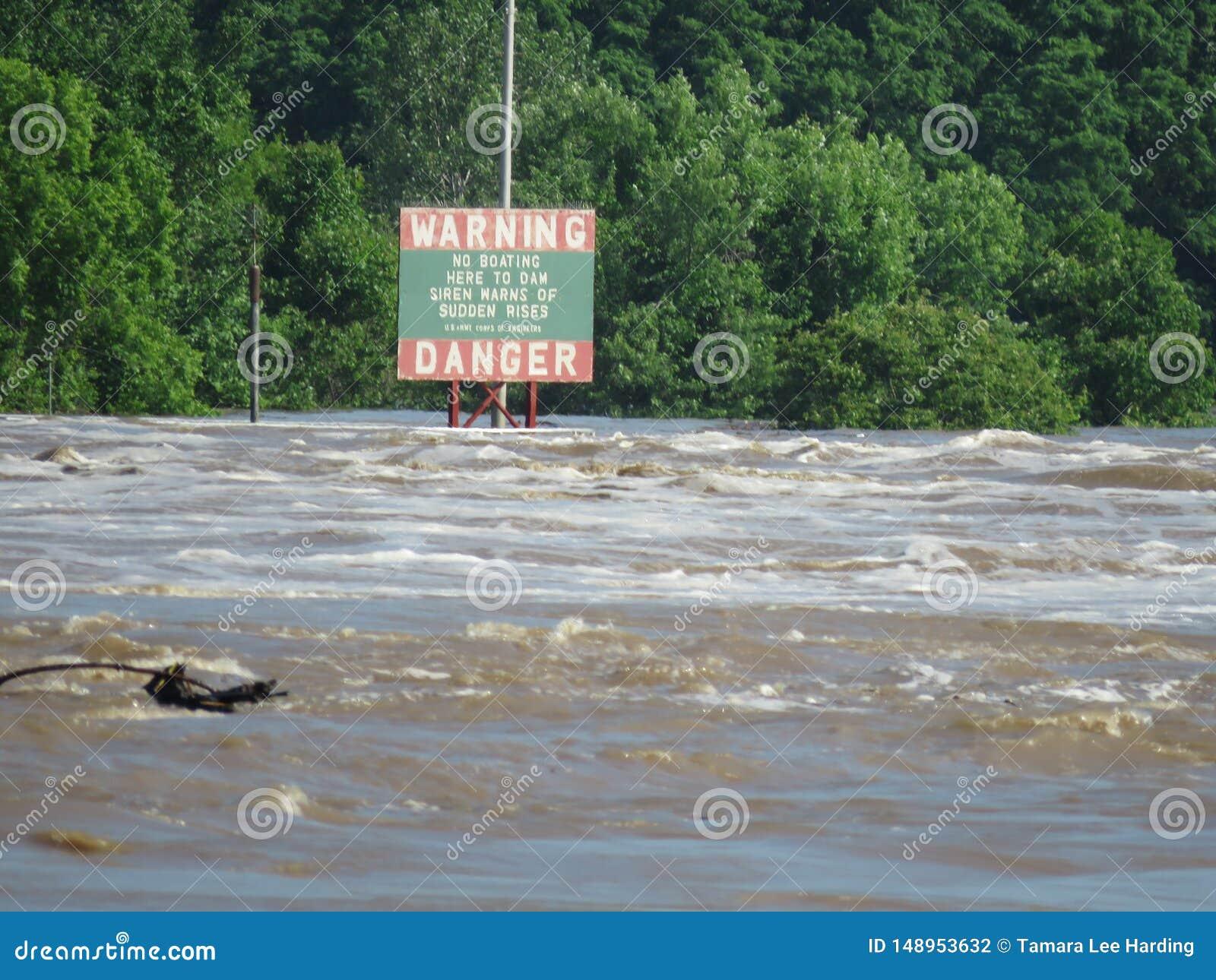 Aviso, sinal do perigo perto da represa no Arkansas River